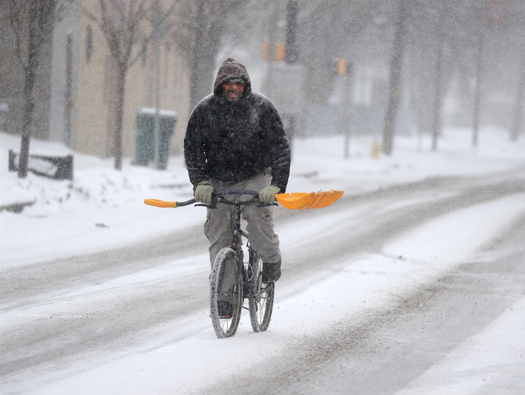 A man rides his bike while the snow starts to fall in Rochester Saturday morning.