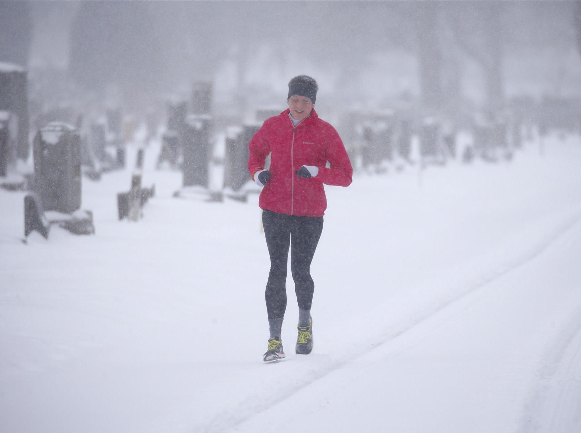 Ashley Peppriell, a graduate student at the University of Rochester, runs through Mount Hope Cemetery as heavy snow moves into the area.