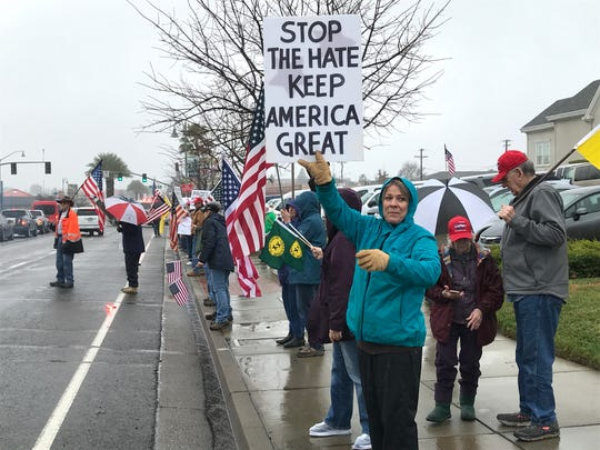 Demonstrators show their support for President Trump's push for a border wall on a drizzly Saturday in front of the Holiday Inn in Redding.