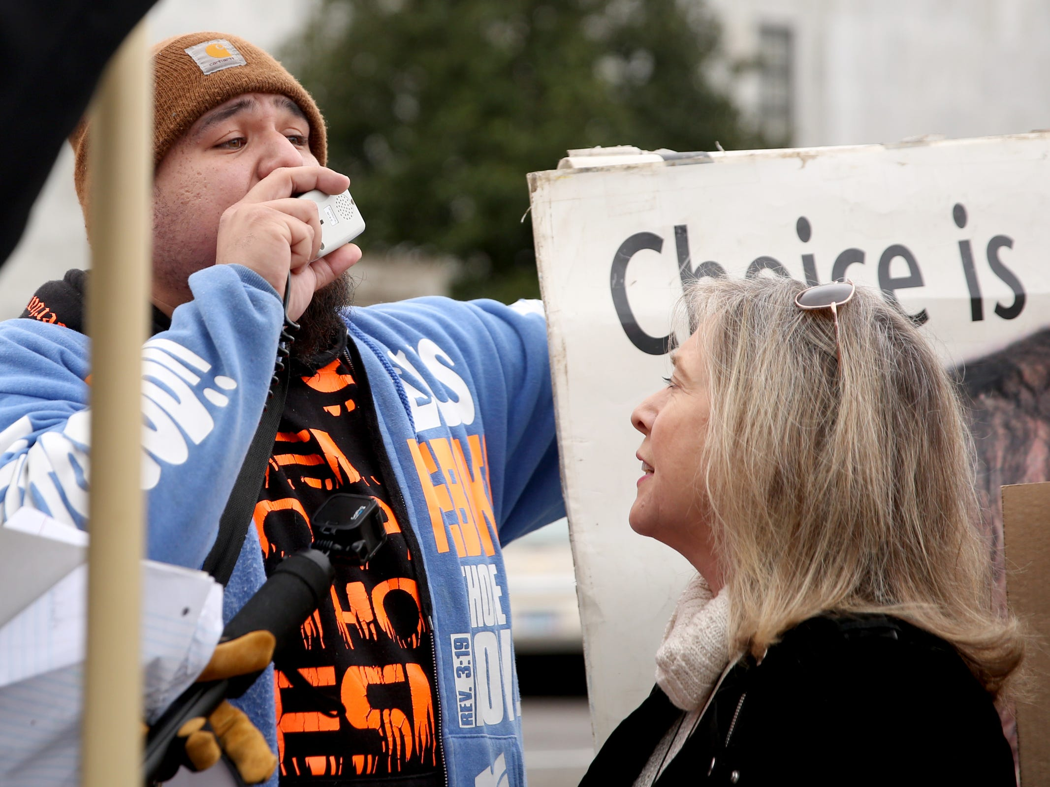 A counter-protester who gave the name St. Templar uses a megaphone to try and drown out speakers, including Warren Binford, at the Women's March Salem outside the Oregon State Capitol on Saturday, Jan. 19, 2019.