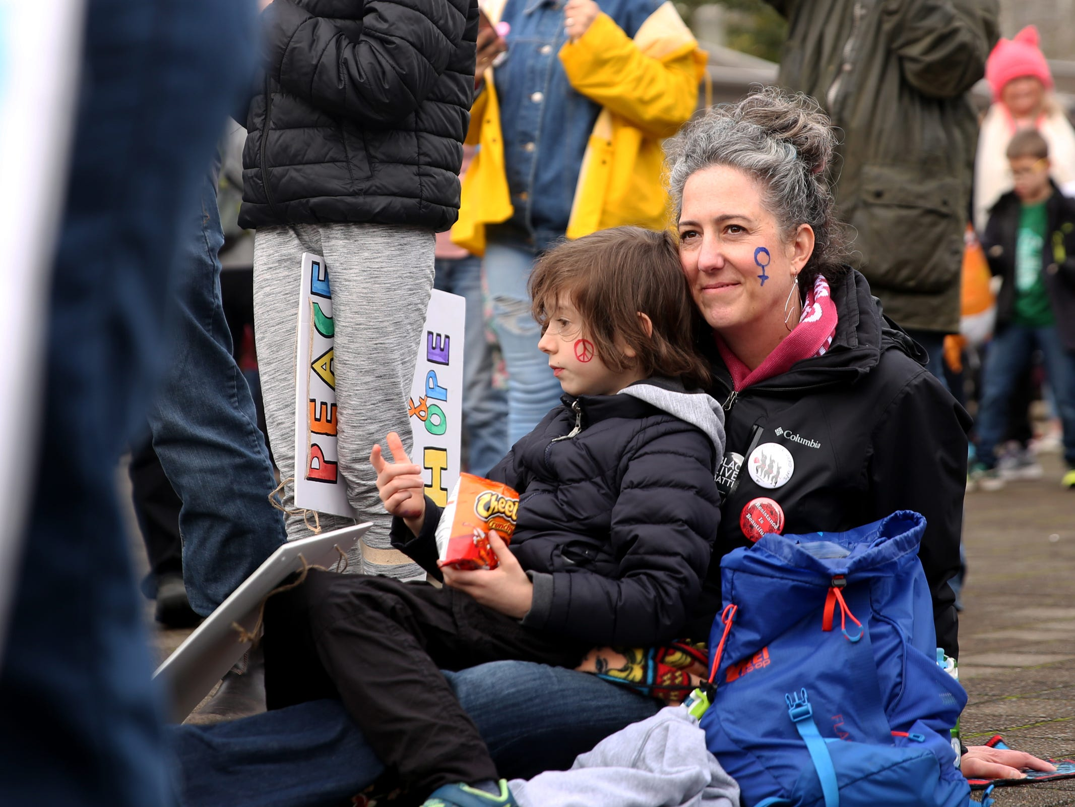 Chris Babinec, of Portland, sits with her son, Canyon Babinec-Love, 6, during the Women's March Salem outside the Oregon State Capitol on Saturday, Jan. 19, 2019.