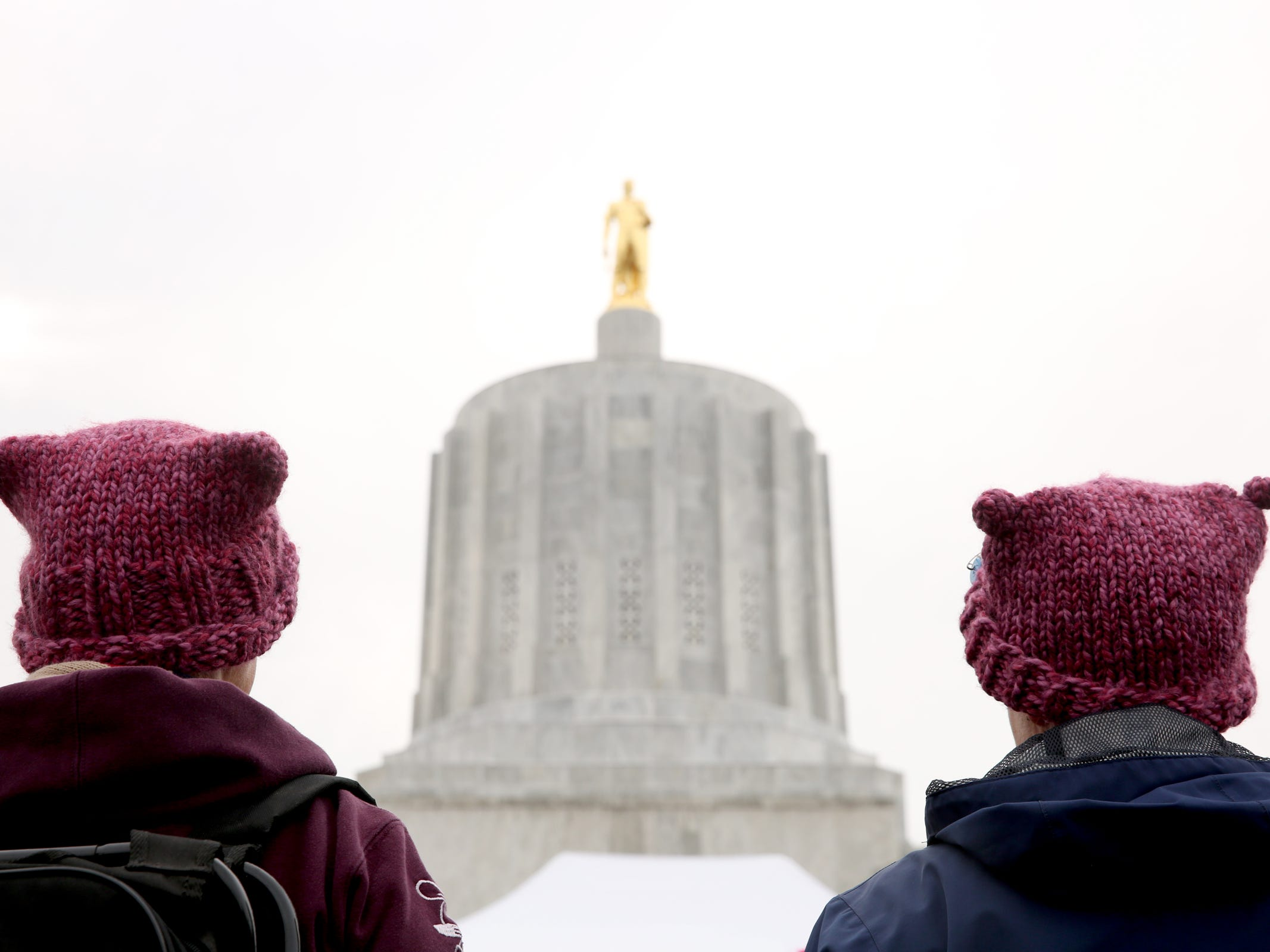 Kate O'Neil, left, and Jill Coleman, both of Dallas, wear pussy hats at Women's March Salem outside the Oregon State Capitol on Saturday, Jan. 19, 2019.