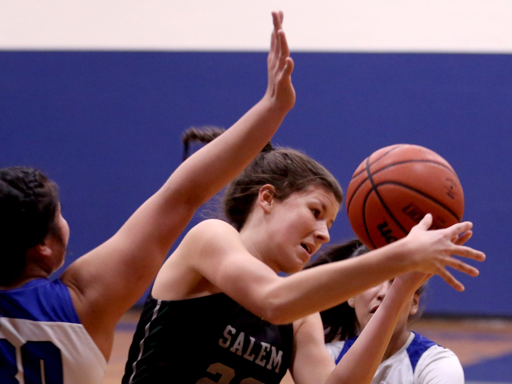 Salem Academy's Chloe Baker (22) grabs a rebound between Blanchet Catholic's Kalea Salang (30) and Ana Coronado (23) in the first half of the Salem Academy vs. Blanchet Catholic girls basketball game at Blanchet Catholic School in Salem on Friday, Jan. 18, 2019. Blanchet Catholic won the gam 48-40.
