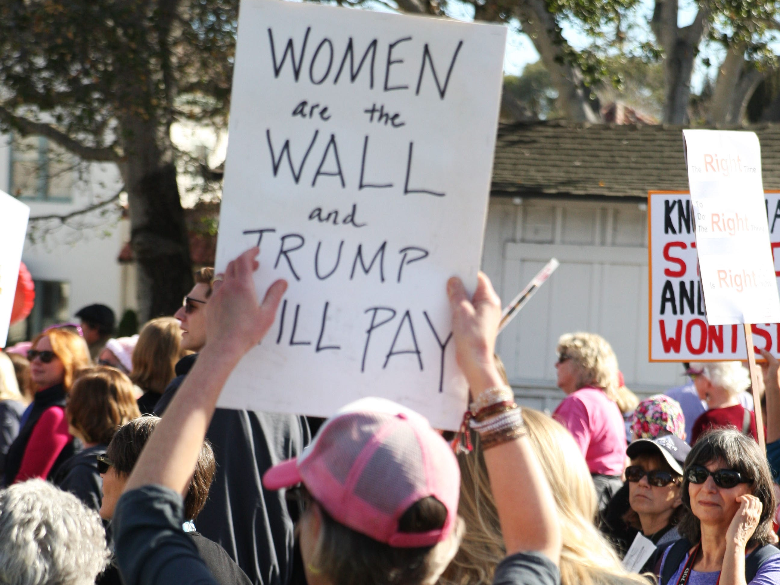 """A woman holds a sign that reads: """"Women are the wall and Trump will pay."""""""