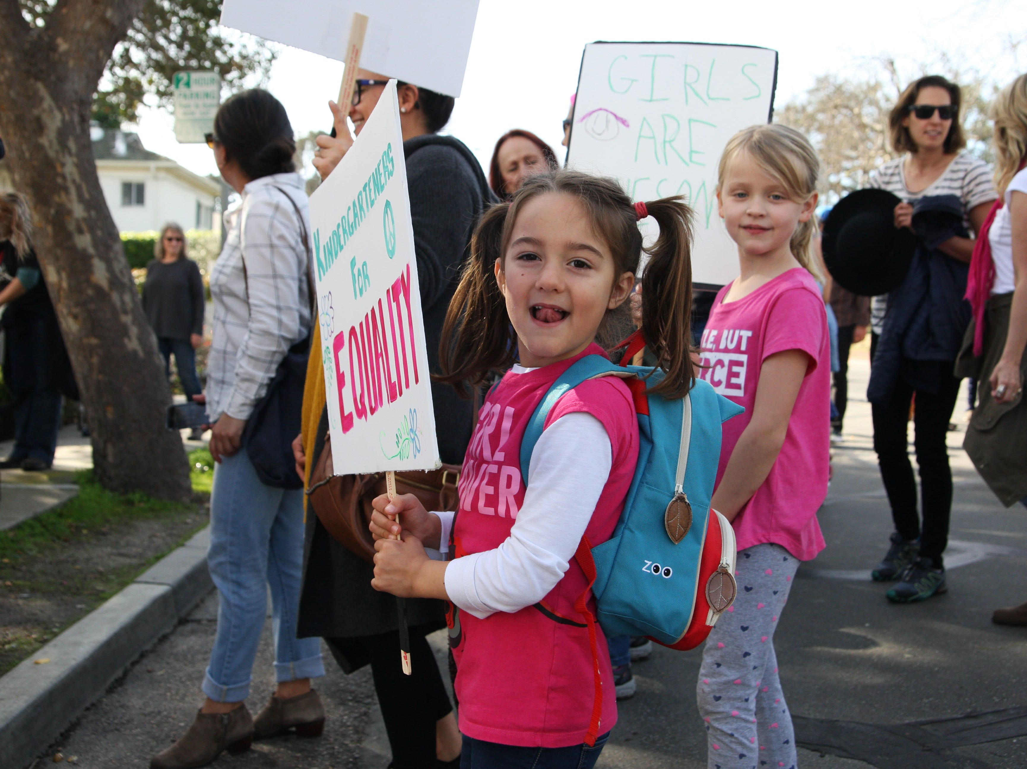 """Penelope Rovick smiles as she shows off her """"Kindergarteners for Equality"""" sign that her father made for her trip to the 2019 Women's March Monterey."""