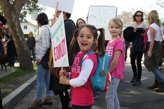 "Penelope Rovick smiles as she shows off her ""Kindergarteners for Equality"" sign that her father made for her trip to the 2019 Women's March Monterey."