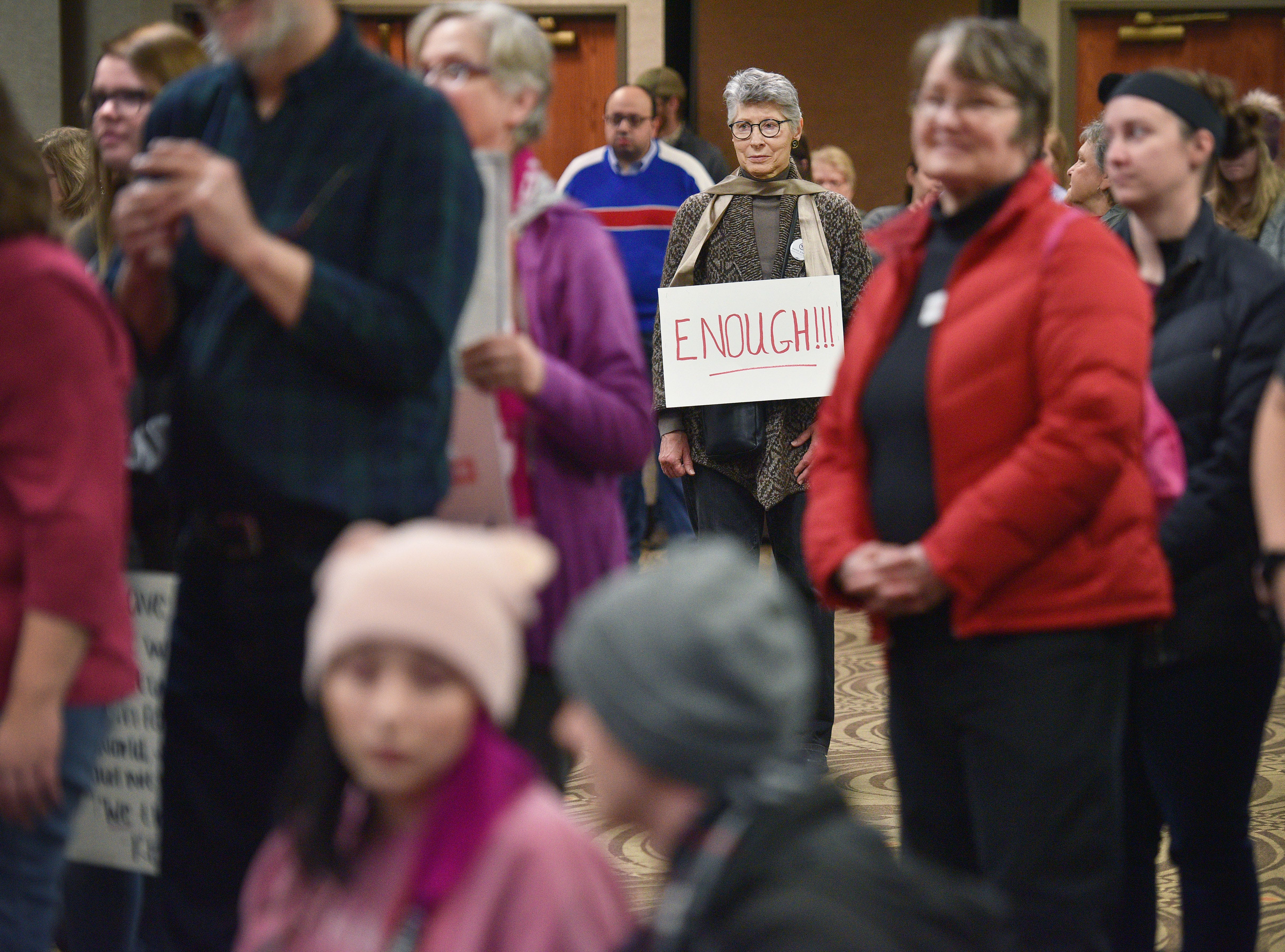 """Catherine Lacey wears a sign that reads, """"enough!!!"""" during the Women's March Saturday, Jan. 19, at the Downtown Sioux Falls Holiday Inn-City Centre in Sioux Falls."""