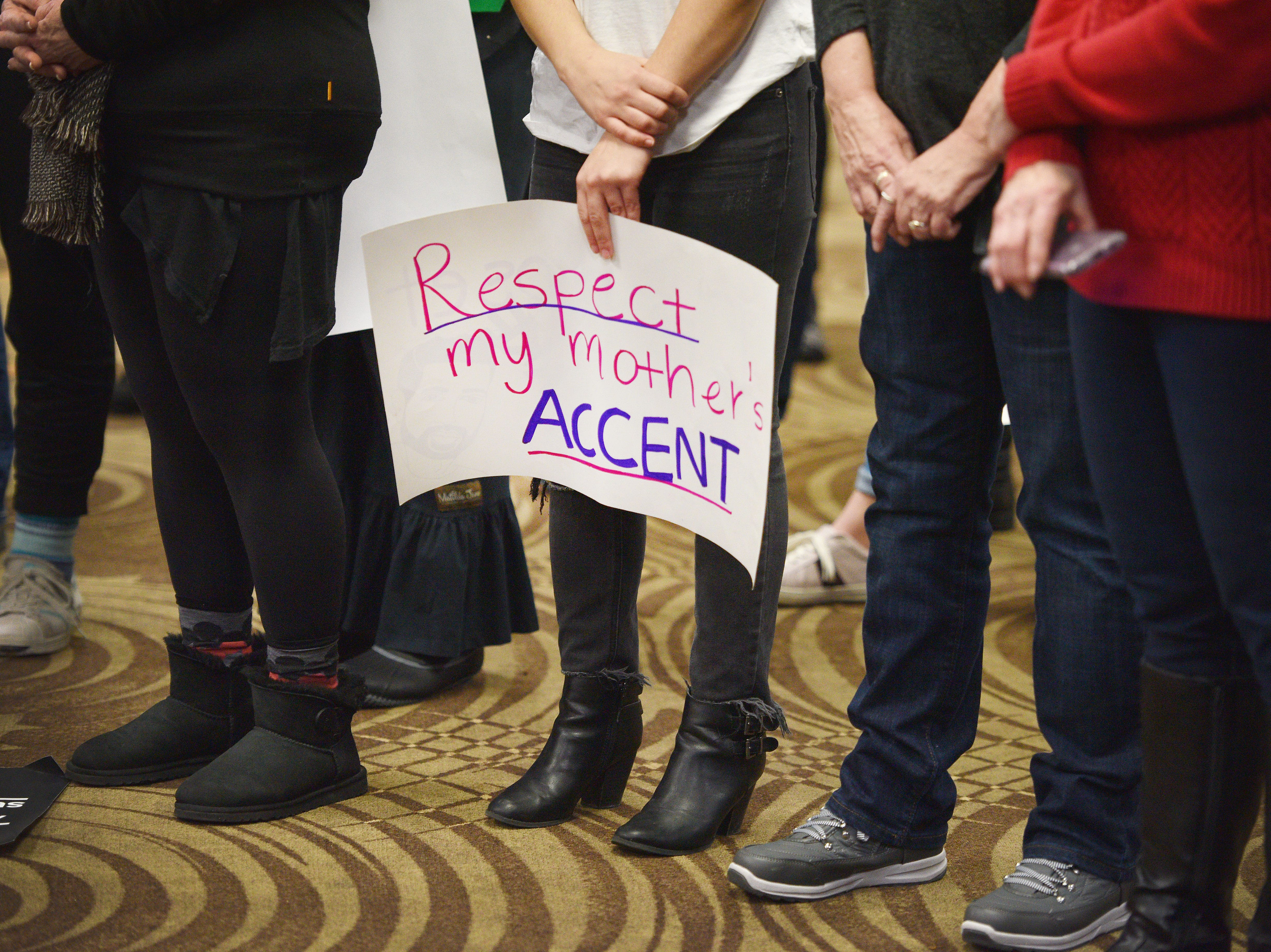 """Chofian Abobakr holds a sign that reads, """"respect my mother's accent"""" during speeches at the Women's March Saturday, Jan. 19, at the Downtown Sioux Falls Holiday Inn-City Centre in Sioux Falls."""