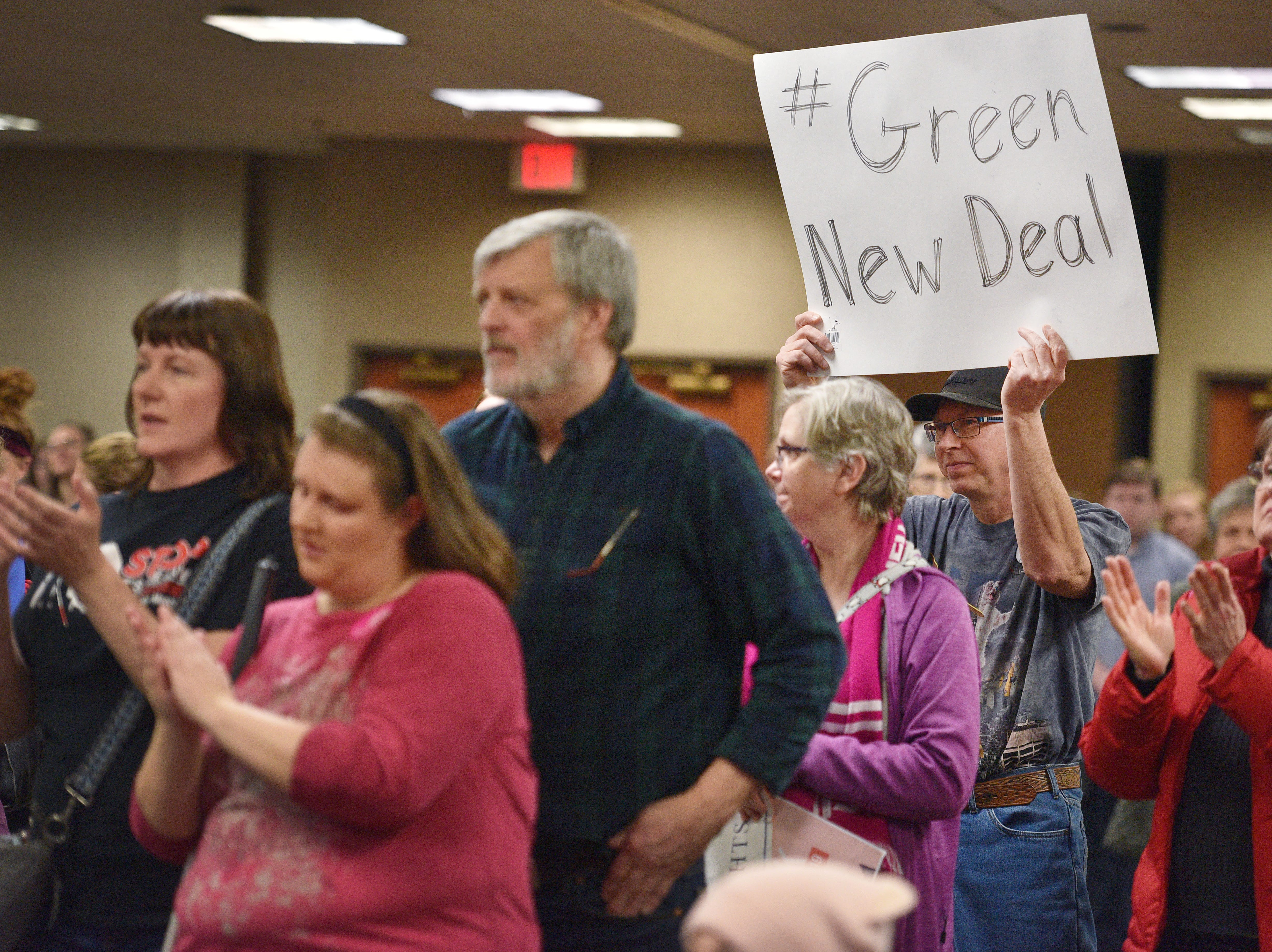 """A man holds a sign that reads """"#green new deal"""" during the Women's March Saturday, Jan. 19, at the Downtown Sioux Falls Holiday Inn-City Centre in Sioux Falls."""