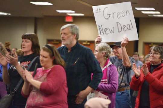 "A man holds a sign that reads ""#green new deal"" during the Women's March Saturday, Jan. 19, at the Downtown Sioux Falls Holiday Inn-City Centre in Sioux Falls."