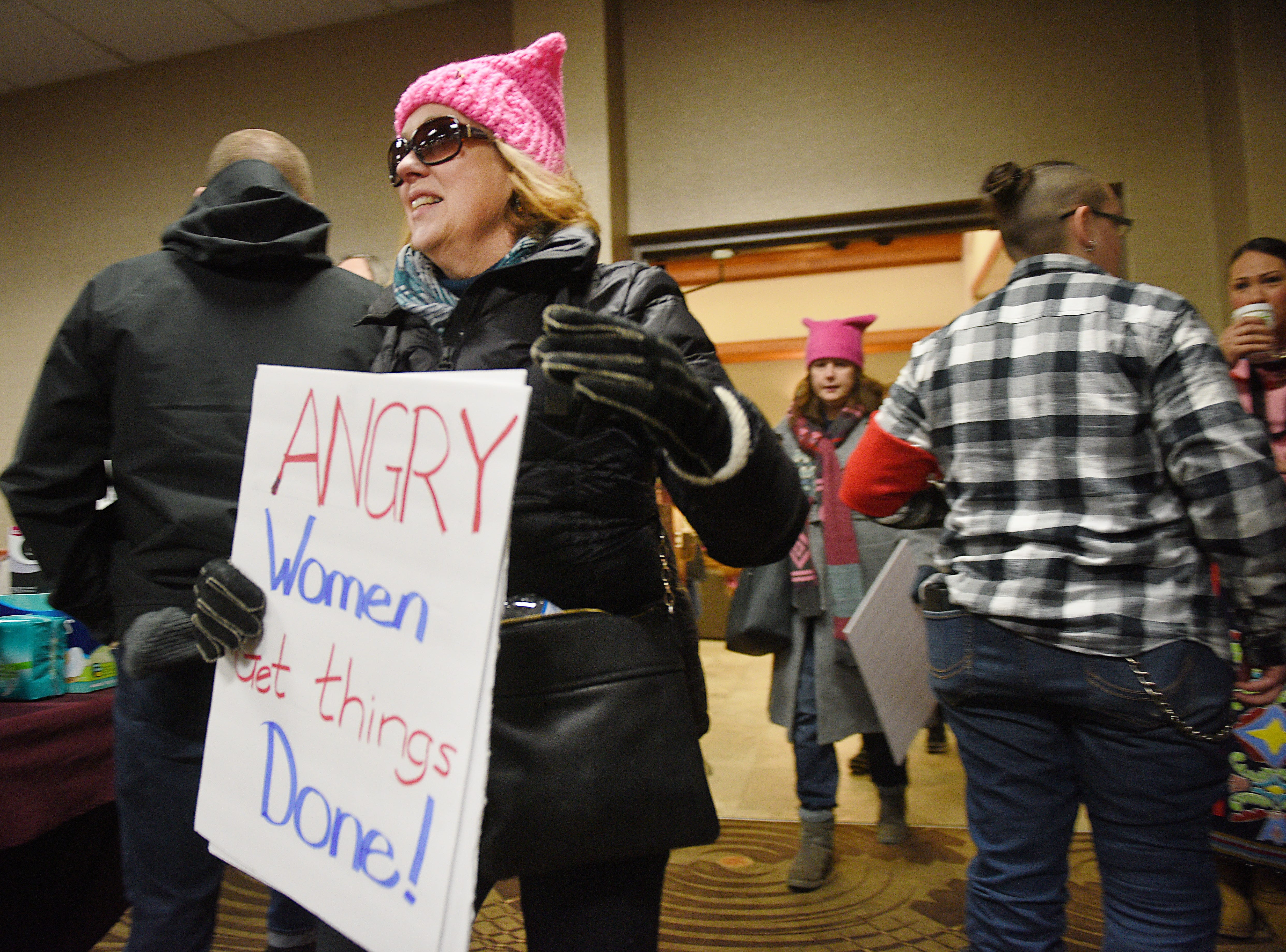 """Sheila Wood walks into the Falls East ballroom with a sign that reads, """"angry women get things done"""" during the Women's March Saturday, Jan. 19, at the Downtown Sioux Falls Holiday Inn-City Centre in Sioux Falls."""