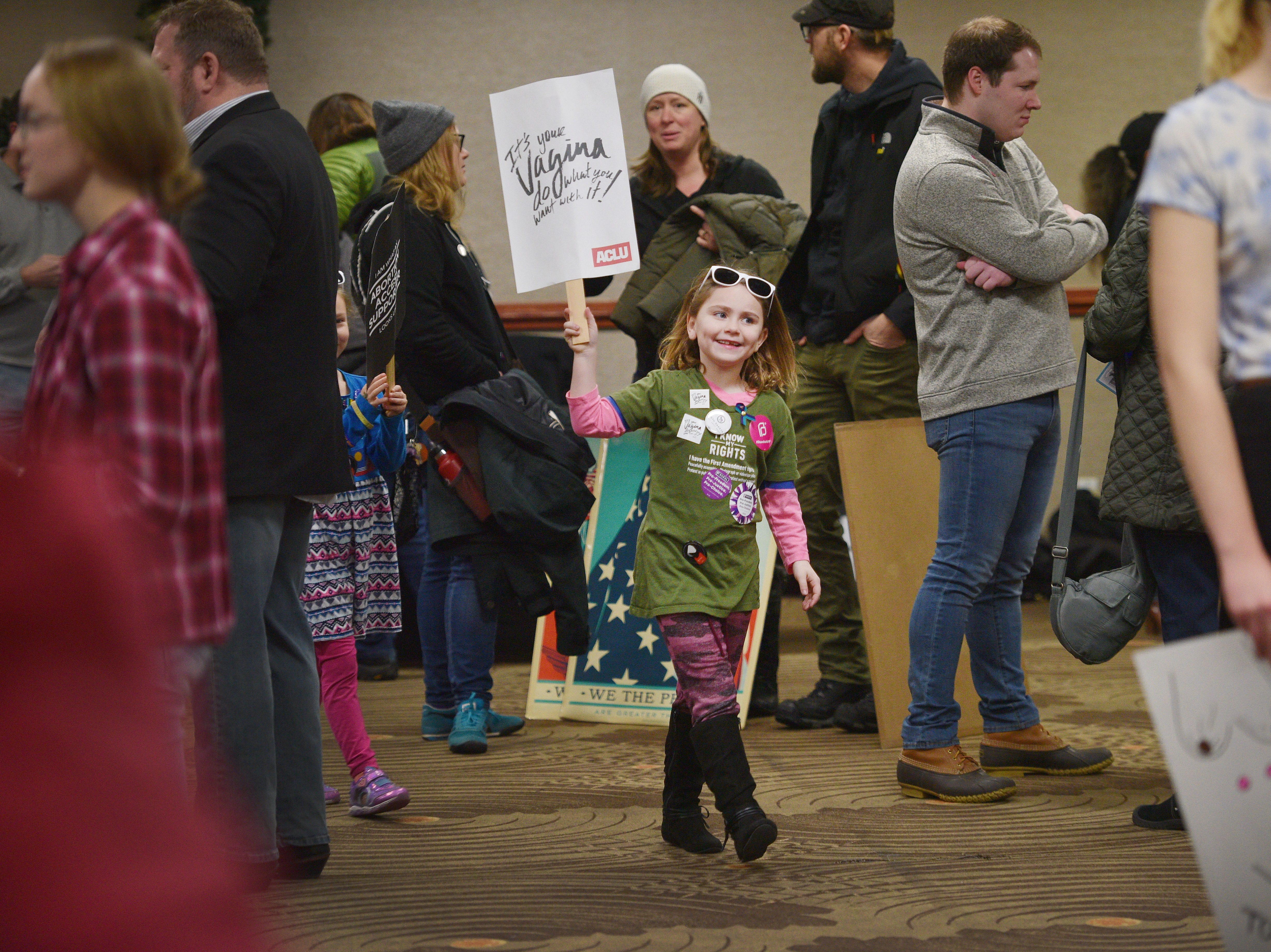 Kate Weissenberger, 7, walks through the Women's March holding an ACLU sign Saturday, Jan. 19, at the Downtown Sioux Falls Holiday Inn-City Centre in Sioux Falls.