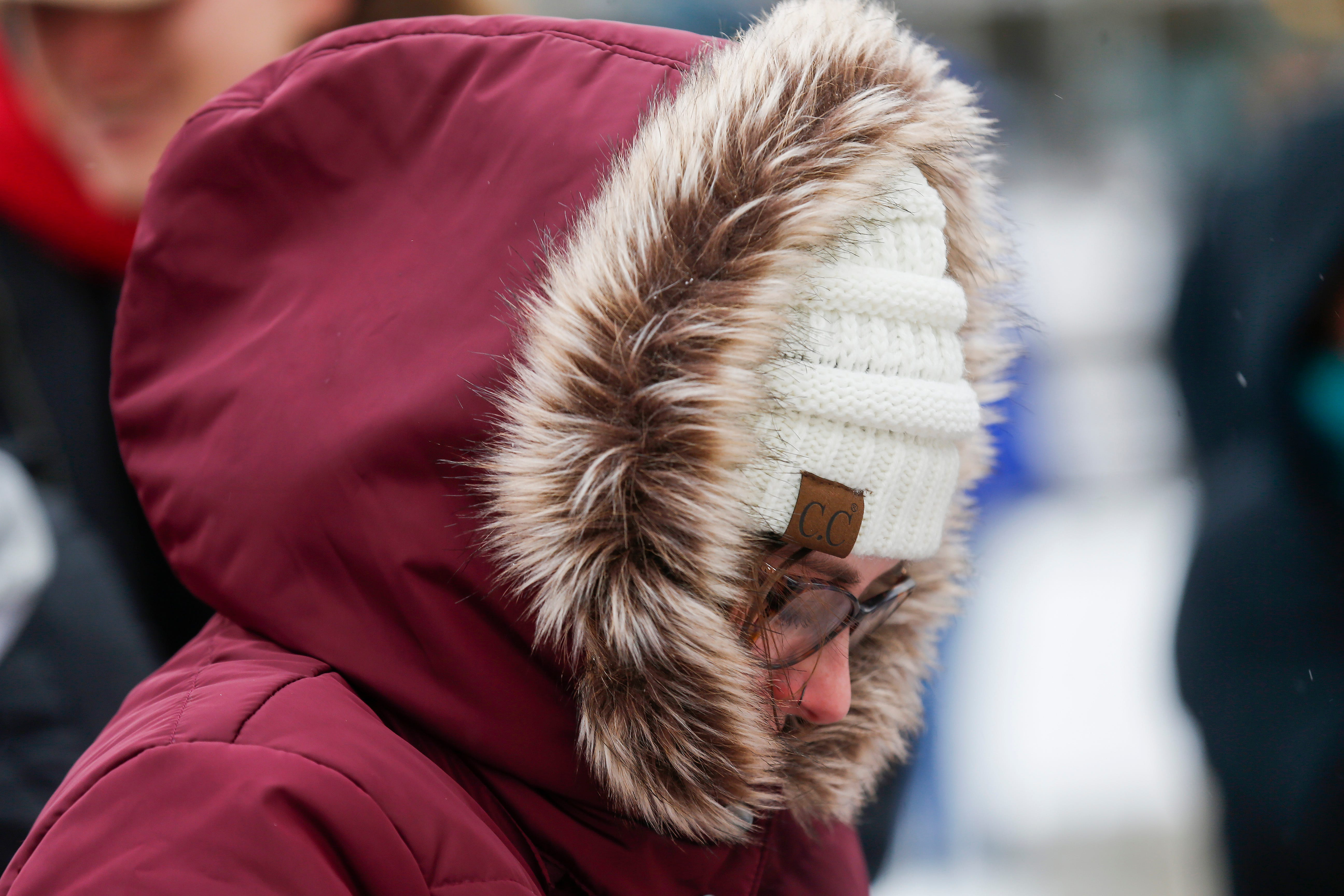 Jordan Harris, president of Me Too Springfield, bundles up for warmth  while listening to speakers during the Women's March at Park Central Square on Saturday, Jan. 19, 2019.