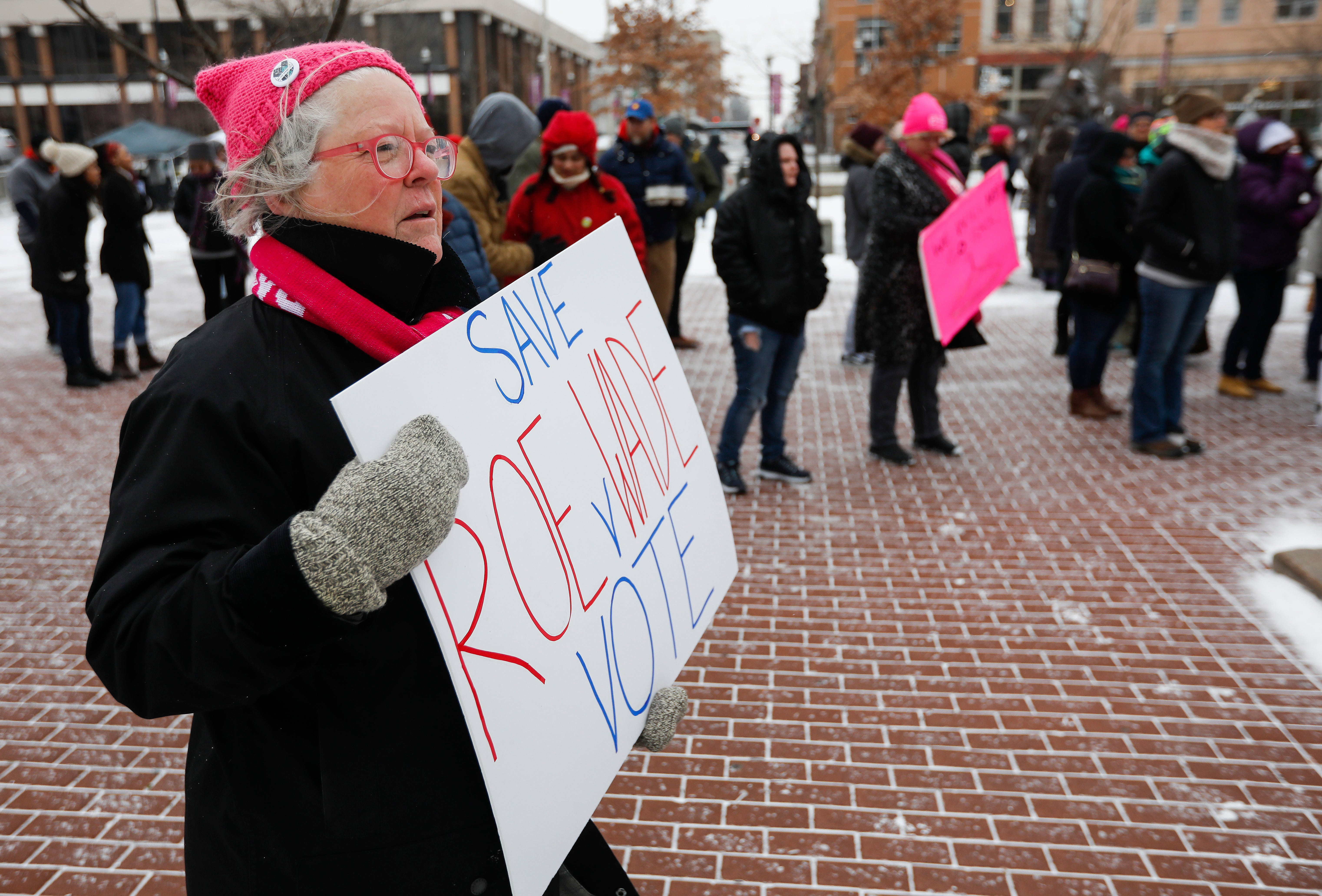 Dee Ogilvy holds up a sign while listening to speakers during the Women's March at Park Central Square on Saturday, Jan. 19, 2019.