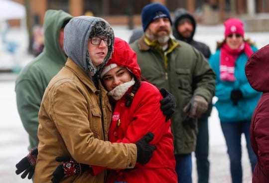 Alex Johnson and Alanis Ballester huddle together for warmth while listening to speakers during the Women's March at Park Central Square on Saturday, Jan. 19, 2019.
