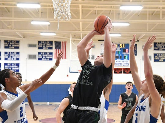 Wilson Memorial's Matt Poole shoots as he is guarded by Robert E. Lee's Treyvn West and Ethan Painter during a game played in Staunton on Friday, Jan. 18, 2019.