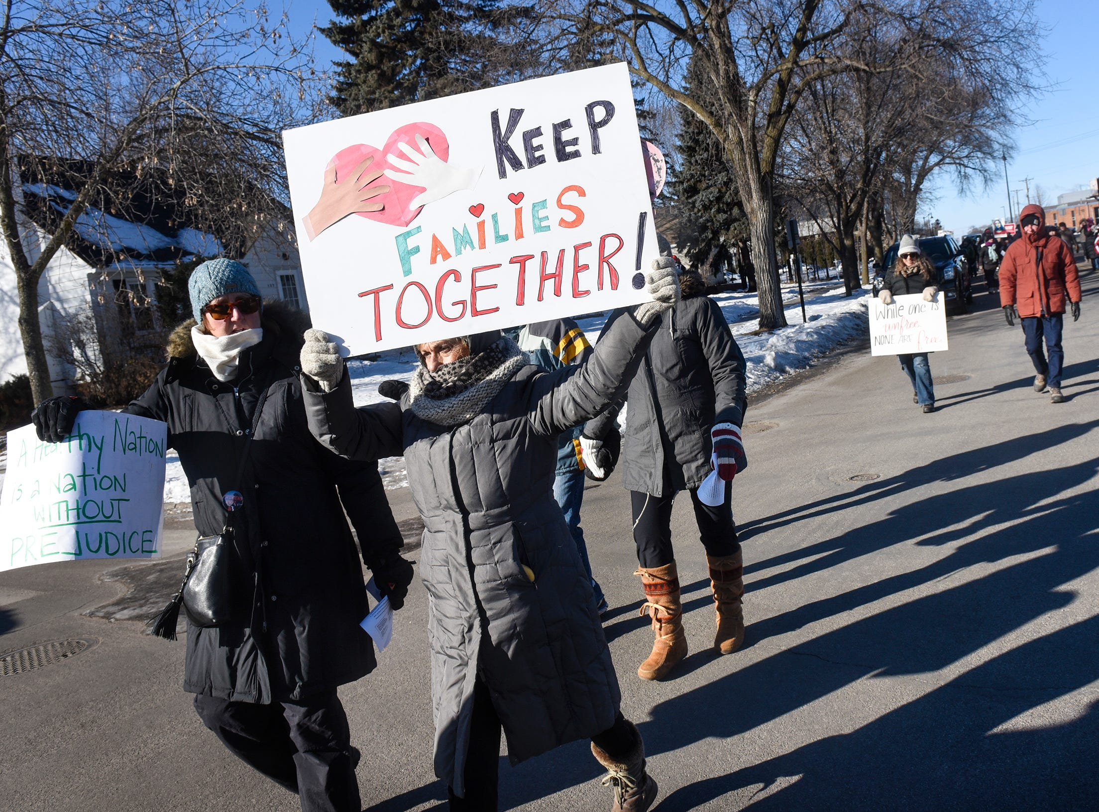 People hold signs during the WomensWave march Saturday, Jan. 19, in St. Cloud.