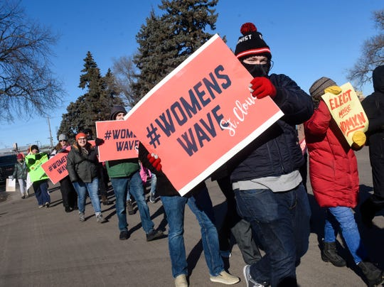 People hold signs while walking in cold temperatures during the WomensWave march Saturday, Jan. 19, in St. Cloud.