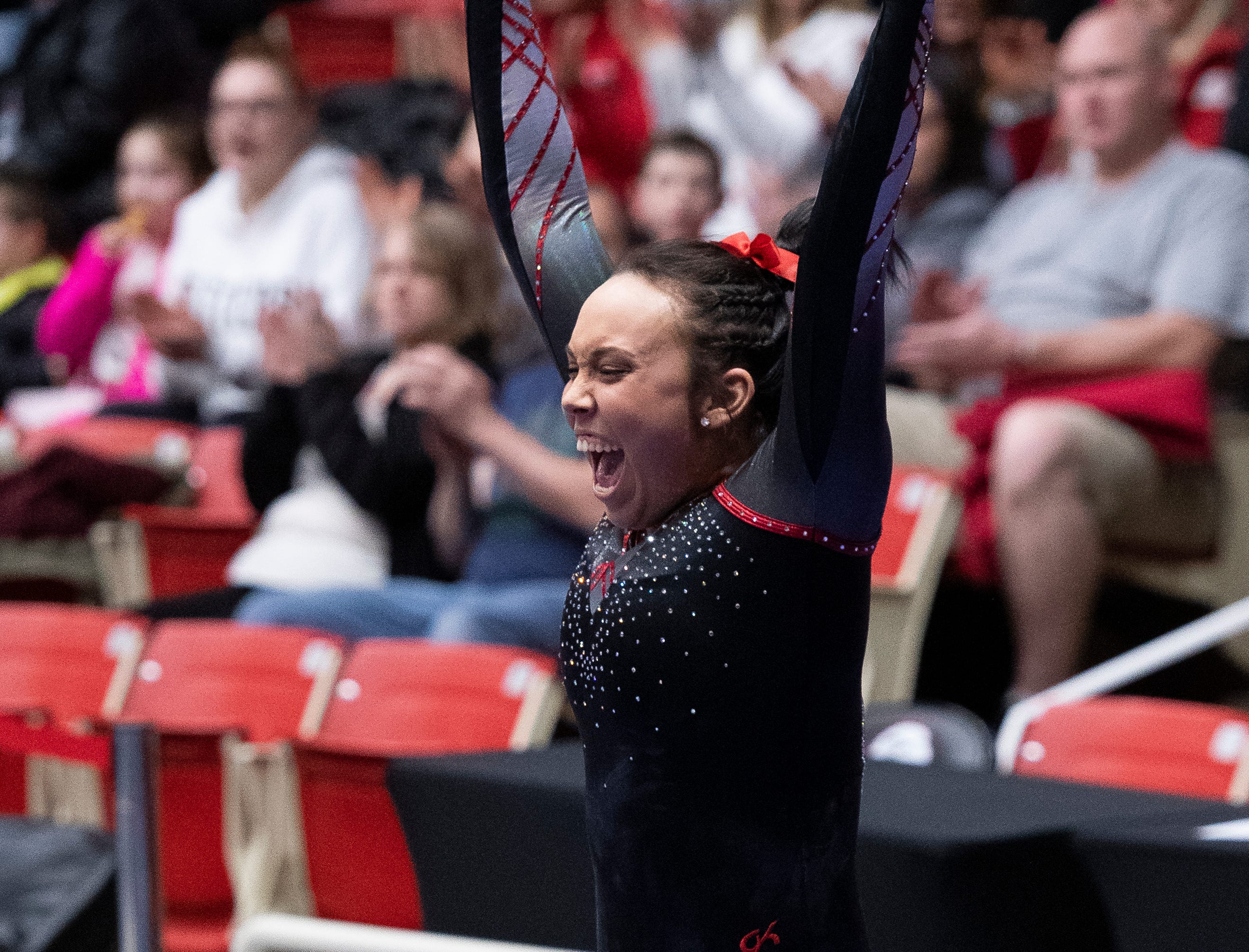 Southern Utah University sophomore Morgan Alfaro celebrates sticking the landing of her vault against Boise State at the America First Event Center Friday, January 18, 2019.