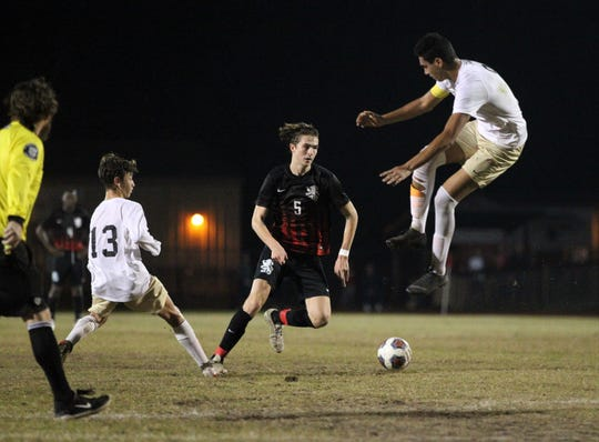 Leon's Collins Proctor dribbles underneath a leaping Buchholz defender as Leon beat Gainesville Buchholz 5-2 on Jan. 18, 2019 to improve to 18-0-1 while being ranked No. 1 nationally.