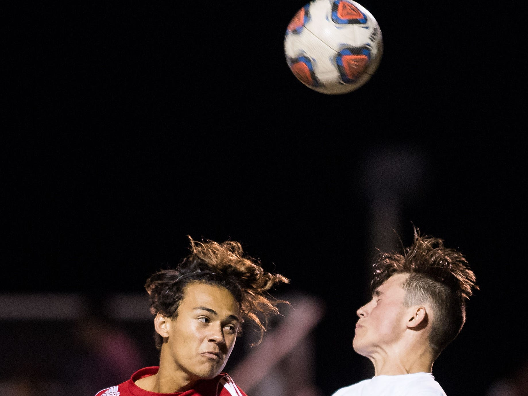 Vero Beach's Chris Rubiano (left) and Okeechobee's Justin Comfort vie for a header during the first half of the high school boys soccer game Friday, Jan. 18, 2019, at Vero Beach High School.
