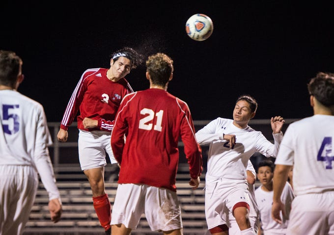 Vero Beach's Justin Raygoza heads the ball towards the goal on a corner kick against Okeechobee, whose goalkeeper Mario Martinez makes the save, during the first half of the high school boys soccer game Friday, Jan. 18, 2019, at Vero Beach High School. Raygoza later scored on a header in the second half.