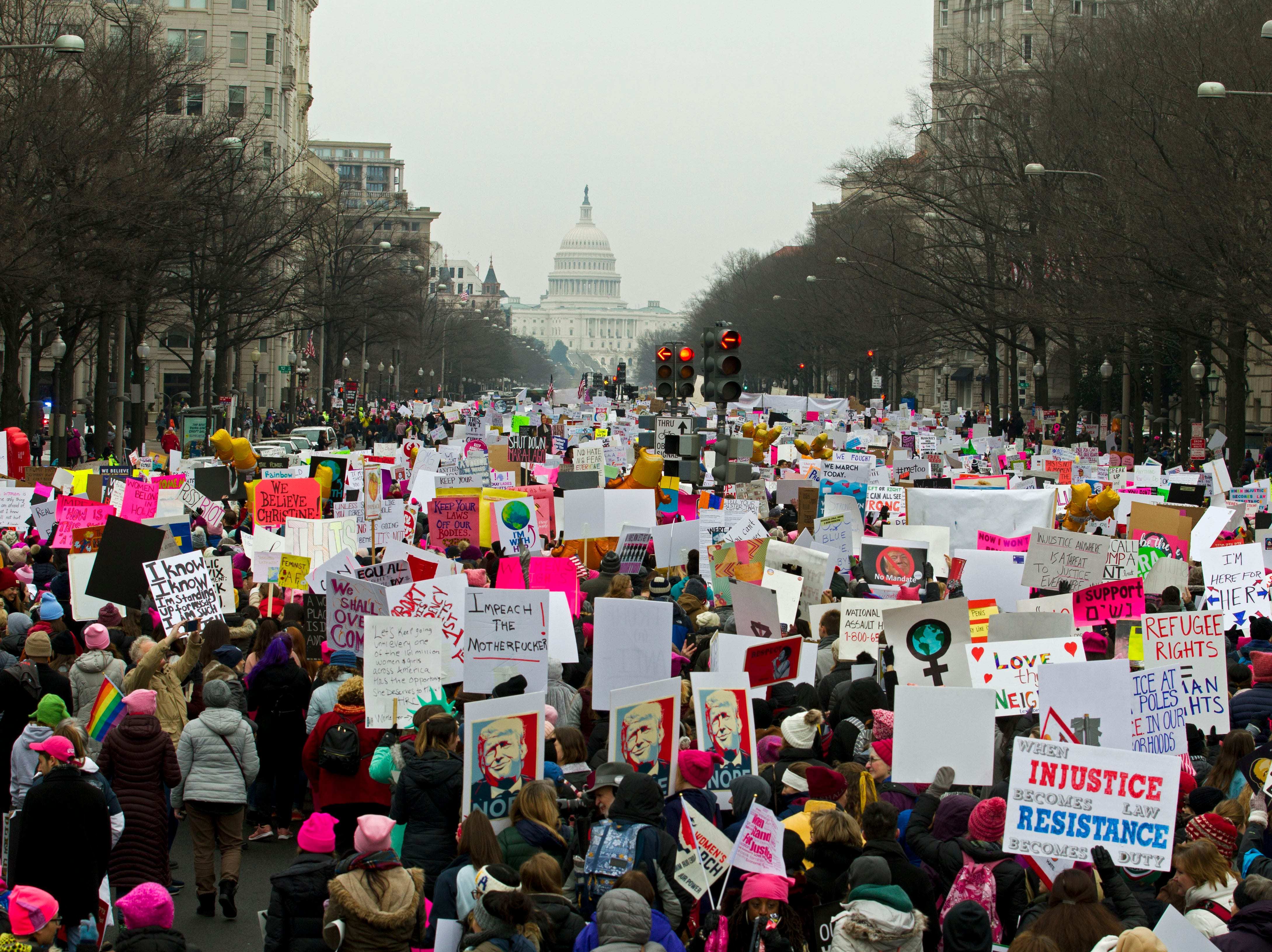 Demonstrators march on Pennsylvania Av. during the Women's March in Washington on Saturday, Jan. 19, 2019.  Organizers had originally planned to gather Saturday on the National Mall, but with the forecast calling for snow and freezing rain Saturday and the National Park Service no longer plowing the snow, the march's location and route was altered this week to start at Freedom Plaza and march down Pennsylvania Avenue past the Trump International Hotel.