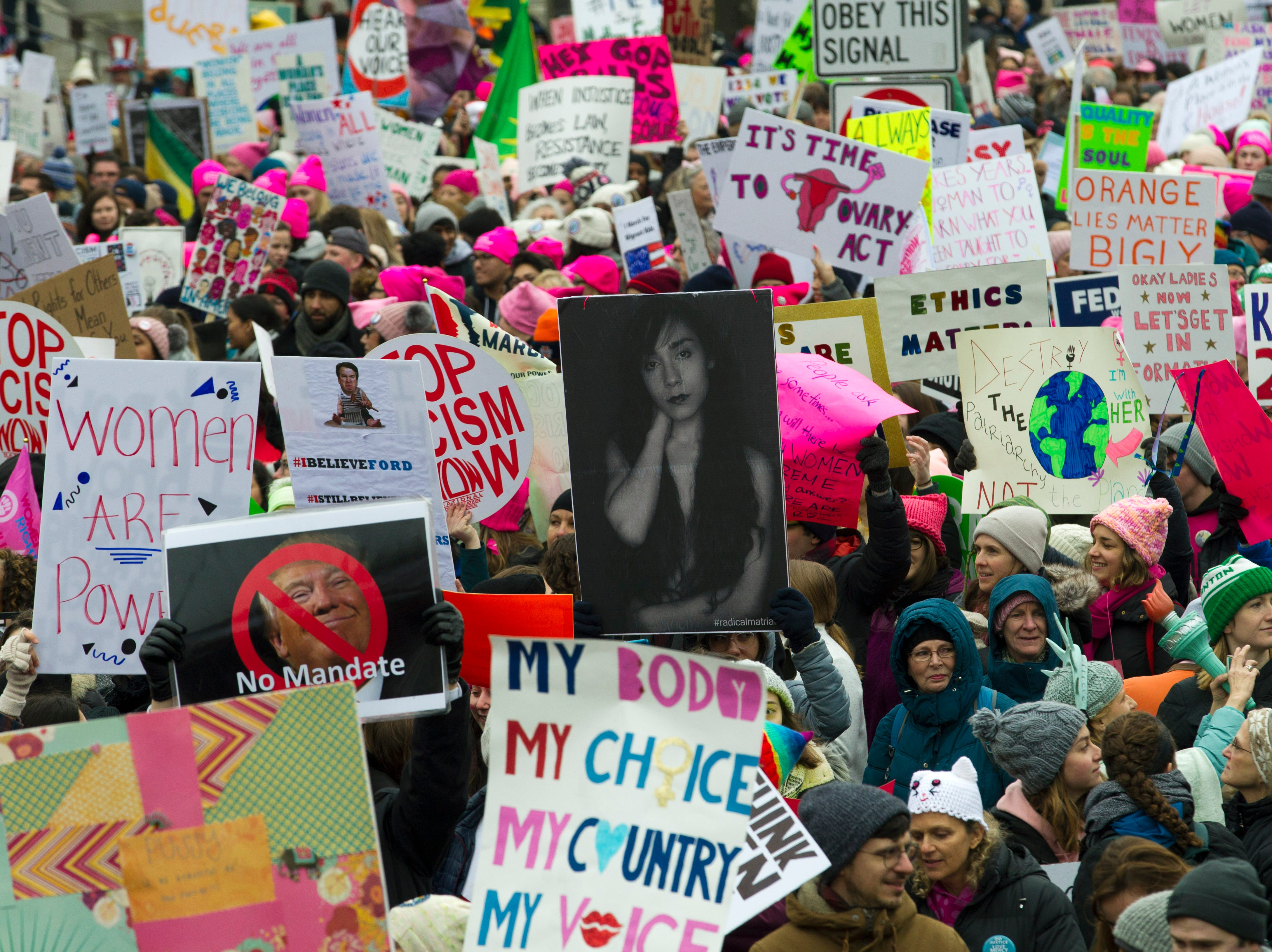 Demonstrators hold signs as they march on Pennsylvania Avenue during the Women's March in Washington on Saturday, Jan. 19, 2019.