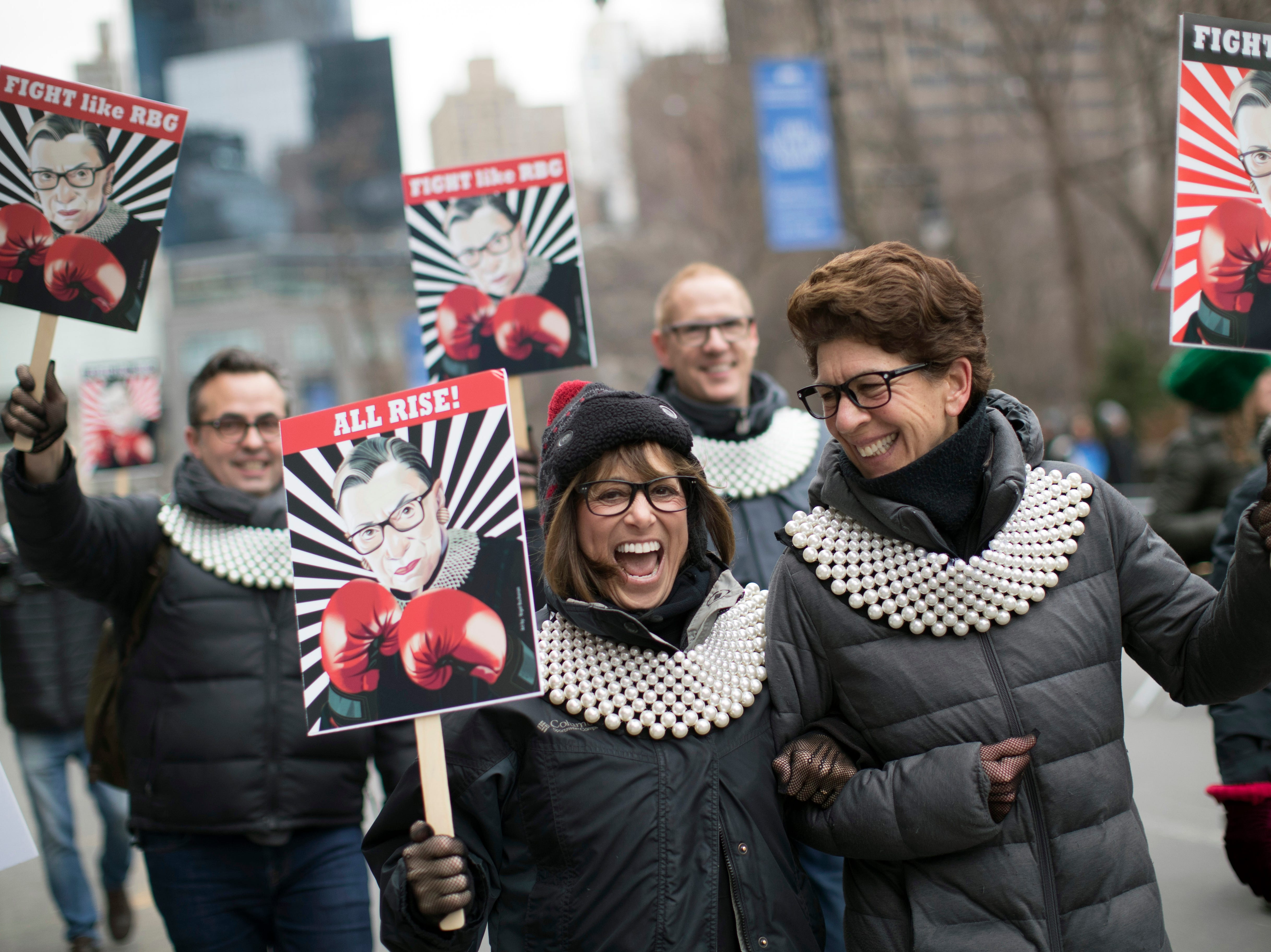 Supporters of Justice Ruth Bader Ginsburg march in during the Women's March Alliance, Saturday, Jan. 19, 2019, in New York. One procession, a march through midtown Manhattan, is being organized by the Women's March Alliance, a nonprofit group whose leaders are putting on their demonstration for the third straight year. Another event, a downtown Manhattan rally held at roughly the same time Saturday, is being organized by the New York City chapter of Women's March Inc., the group formed to help organize the 2017 demonstration in Washington, D.C.