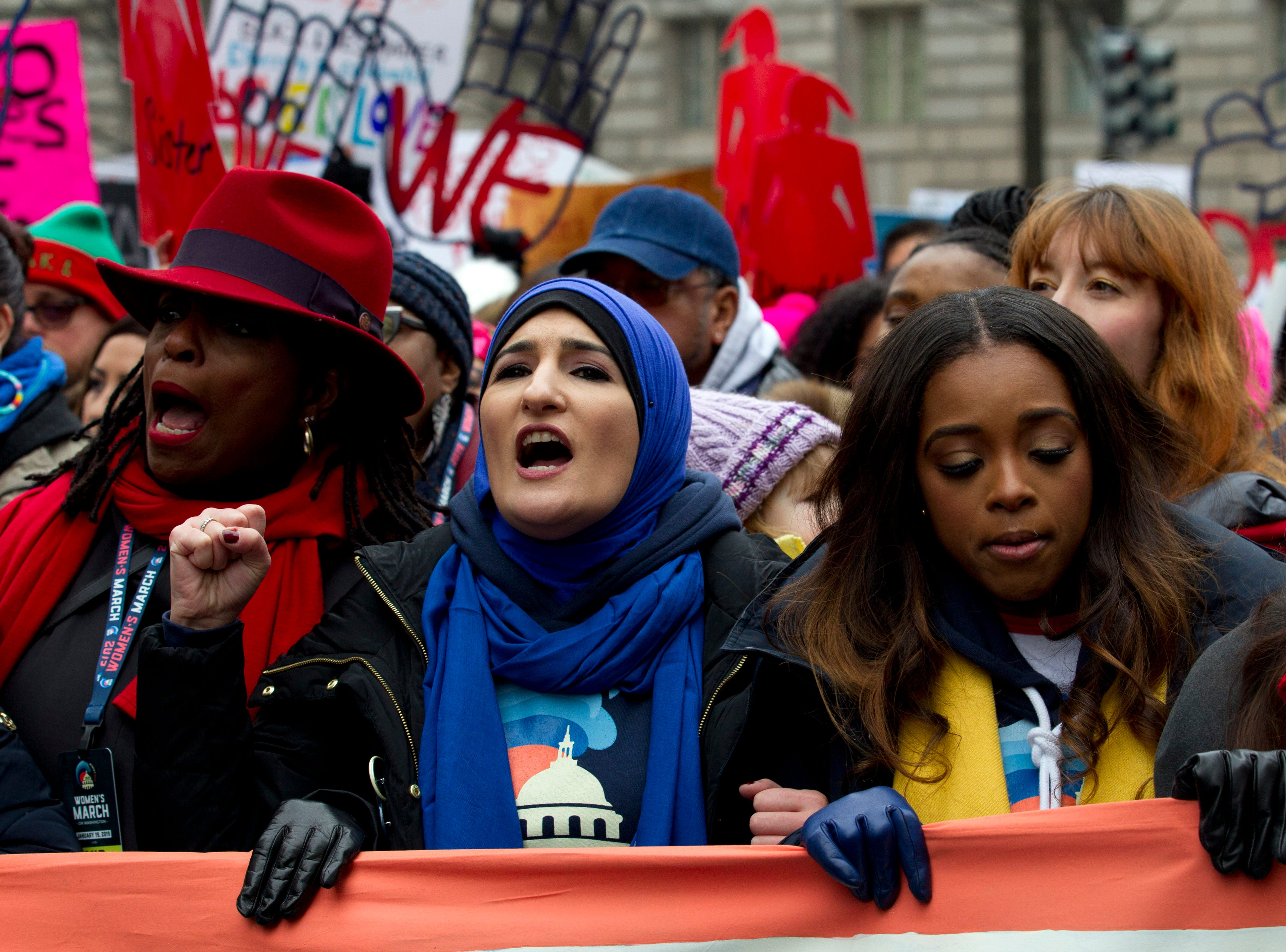 Co-presidents of the 2019 Women's March, Linda Sarsour, center, and Tamika Mallory, right, join other demonstrators on Pennsylvania Avenue during the Women's March in Washington on Saturday, Jan. 19, 2019.