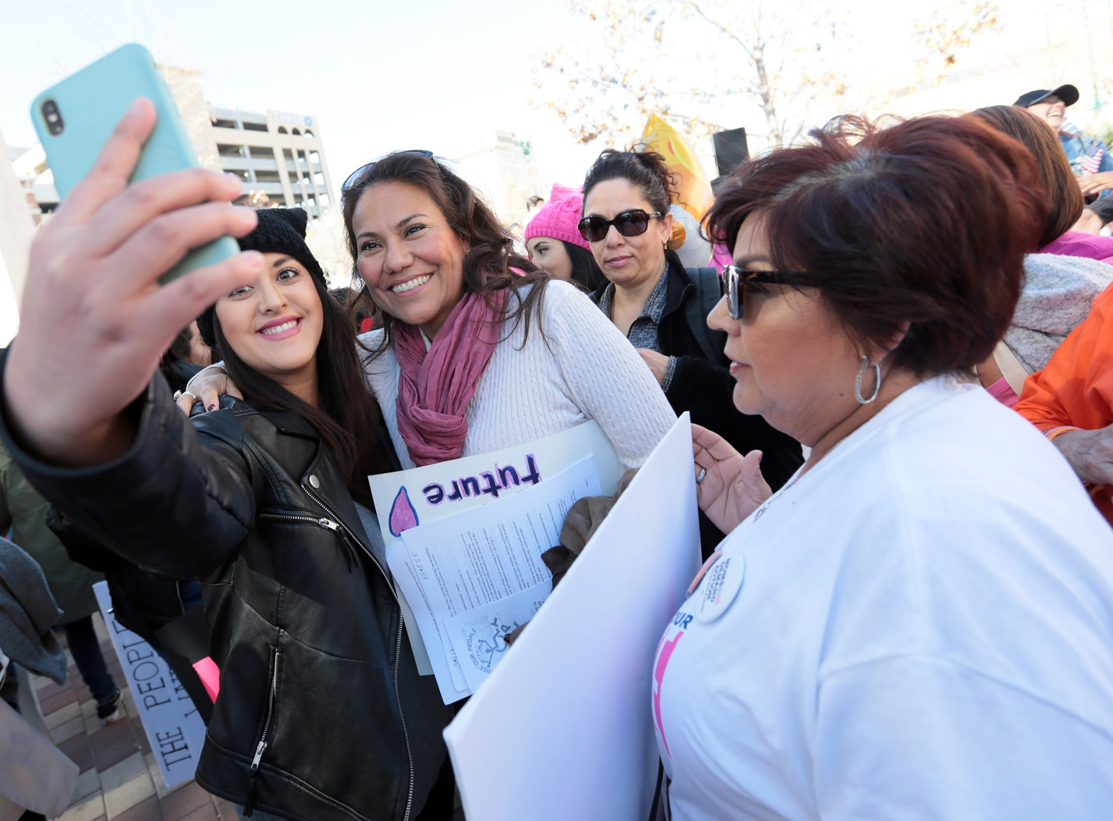 U.S. Rep. Veronica Escobar, D-Texas, takes selfies with supporters during the El Paso Women's March rally at San Jacinto Plaza.