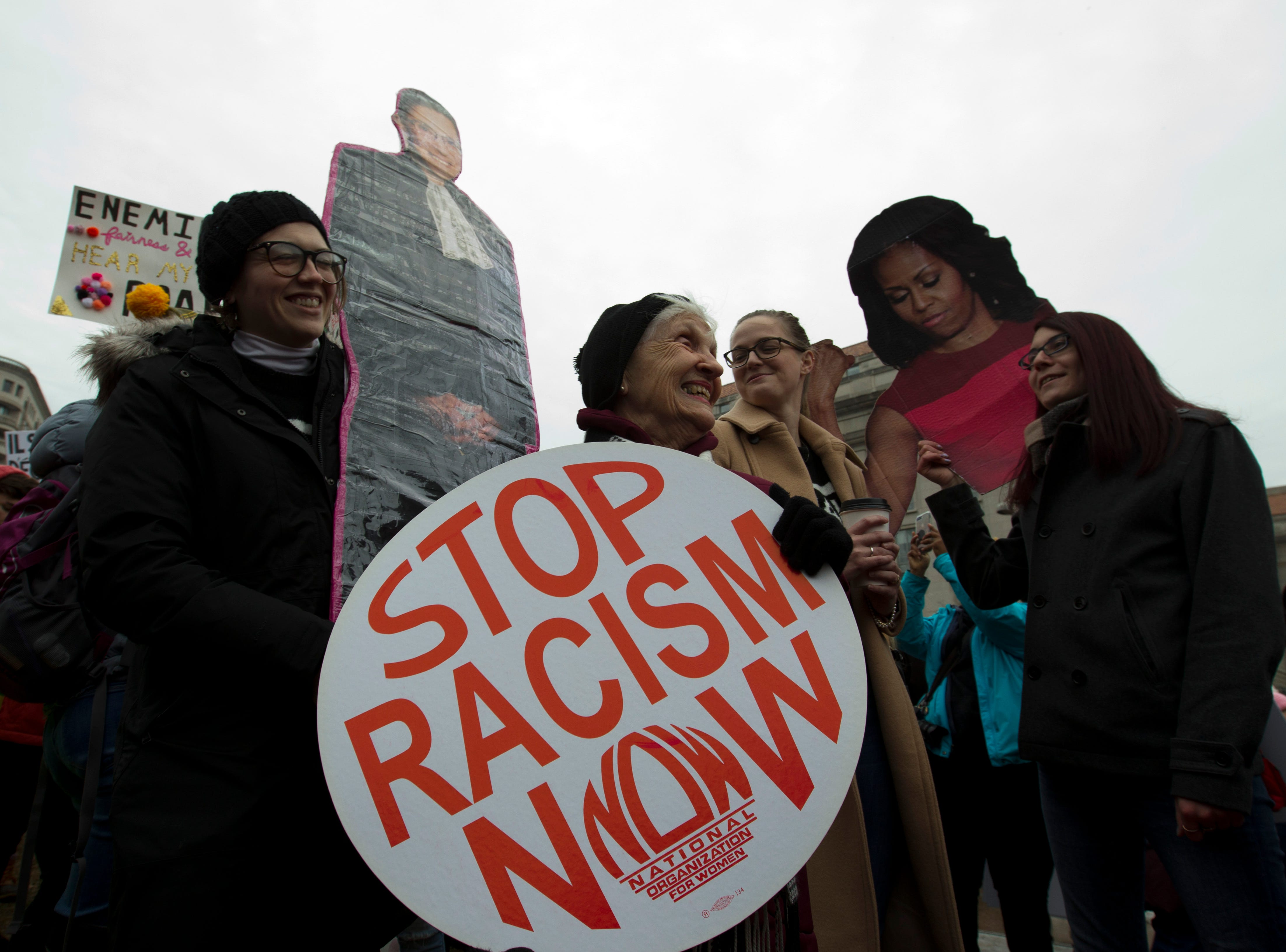 A group hold up signs at freedom plaza during the women's march in Washington on Saturday, Jan. 19, 2019.