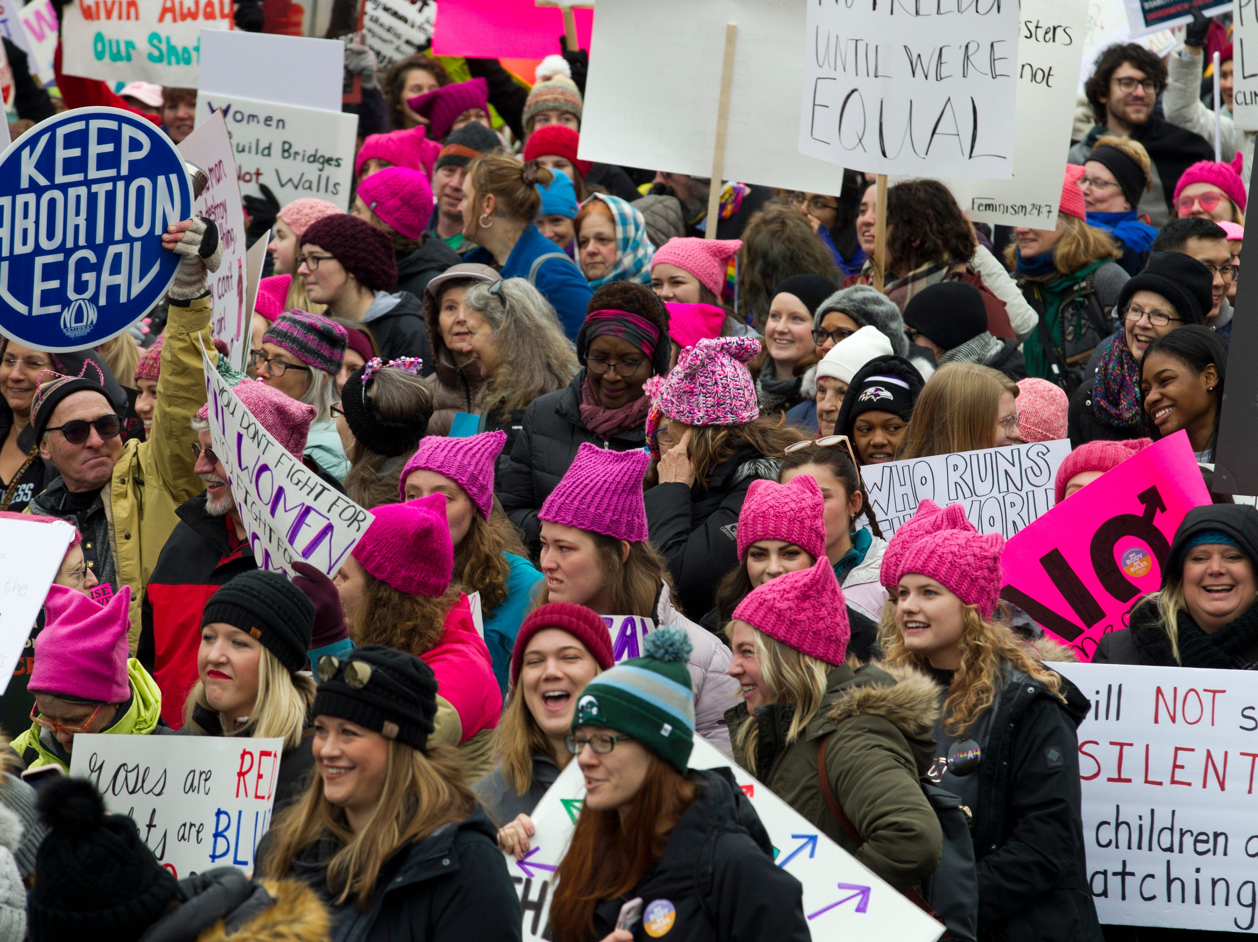 Demonstrators hold up their banners as they march on Pennsylvania Avenue during the Women's March in Washington on Saturday, Jan. 19, 2019.