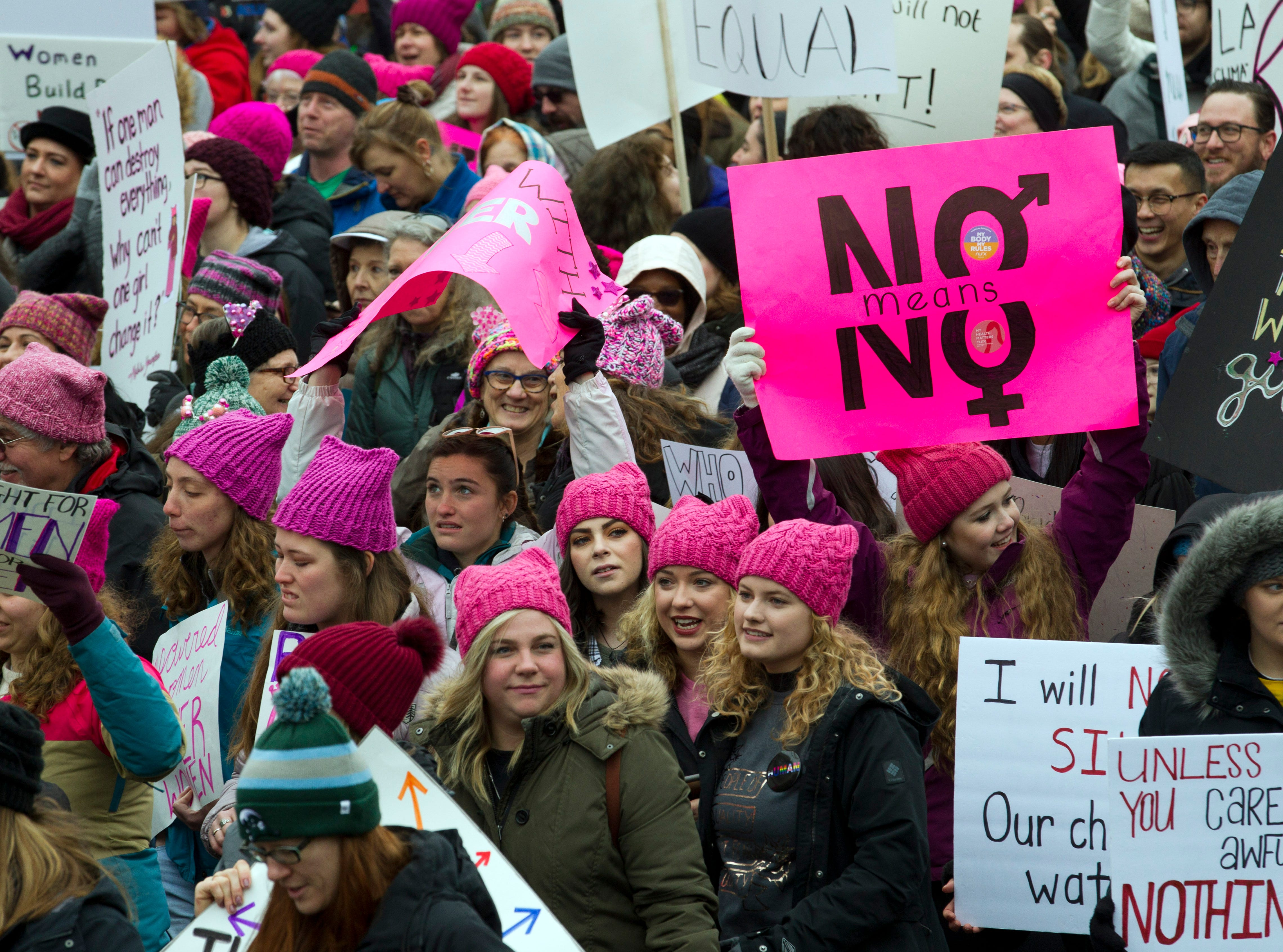 Demonstrators hold banners as they march on Pennsylvania Avenue during the Women's March in Washington on Saturday, Jan. 19, 2019.