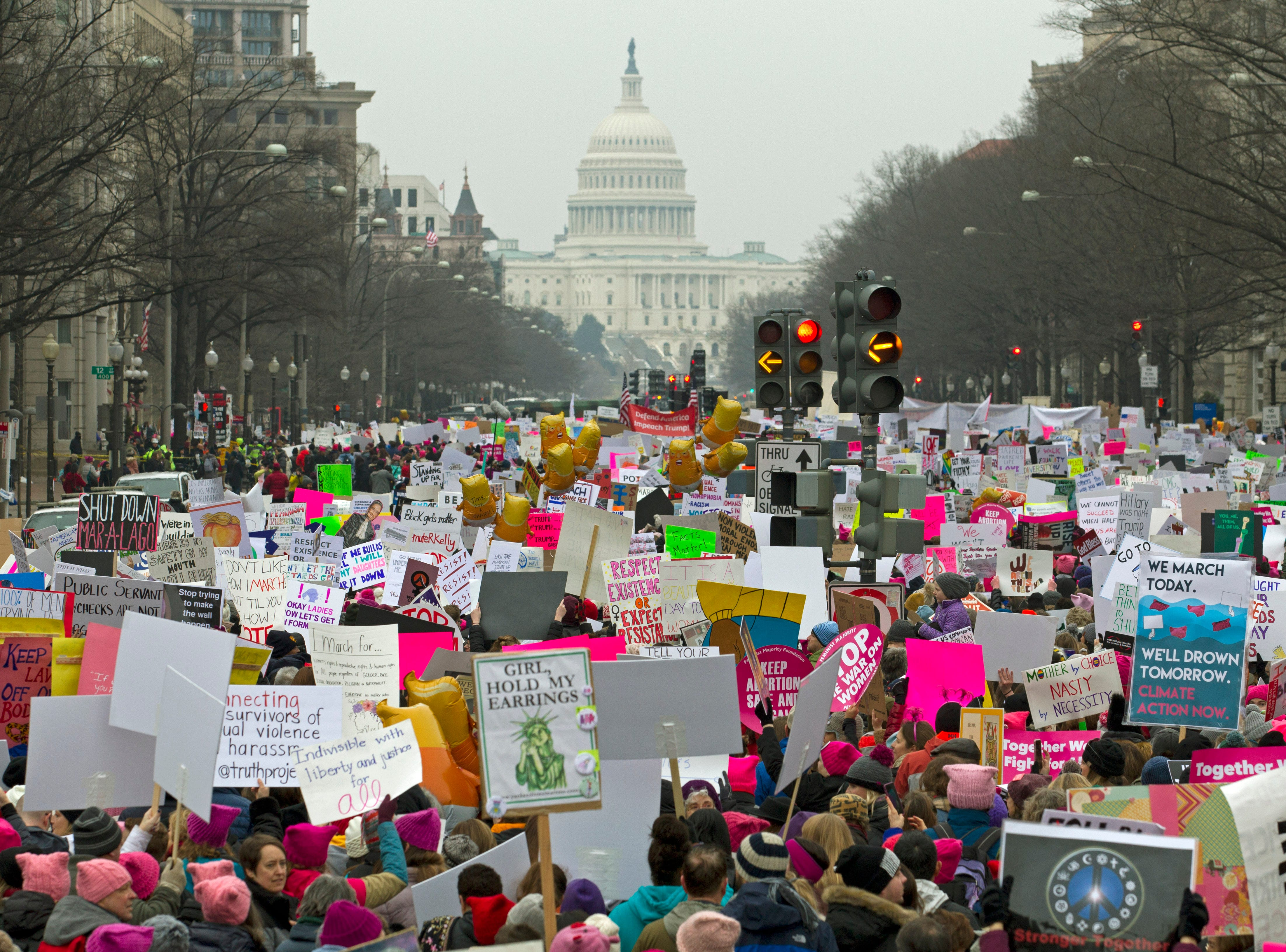 Demonstrators hold signs on Pennsylvania Avenue during the Women's March in Washington on Saturday, Jan. 19, 2019.