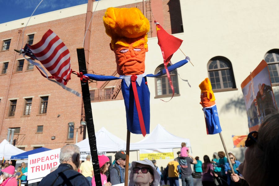 Karen Kitchel carries a puppet created to look like President Donald Trump during the March for Justice in downtown Ventura, Calif.