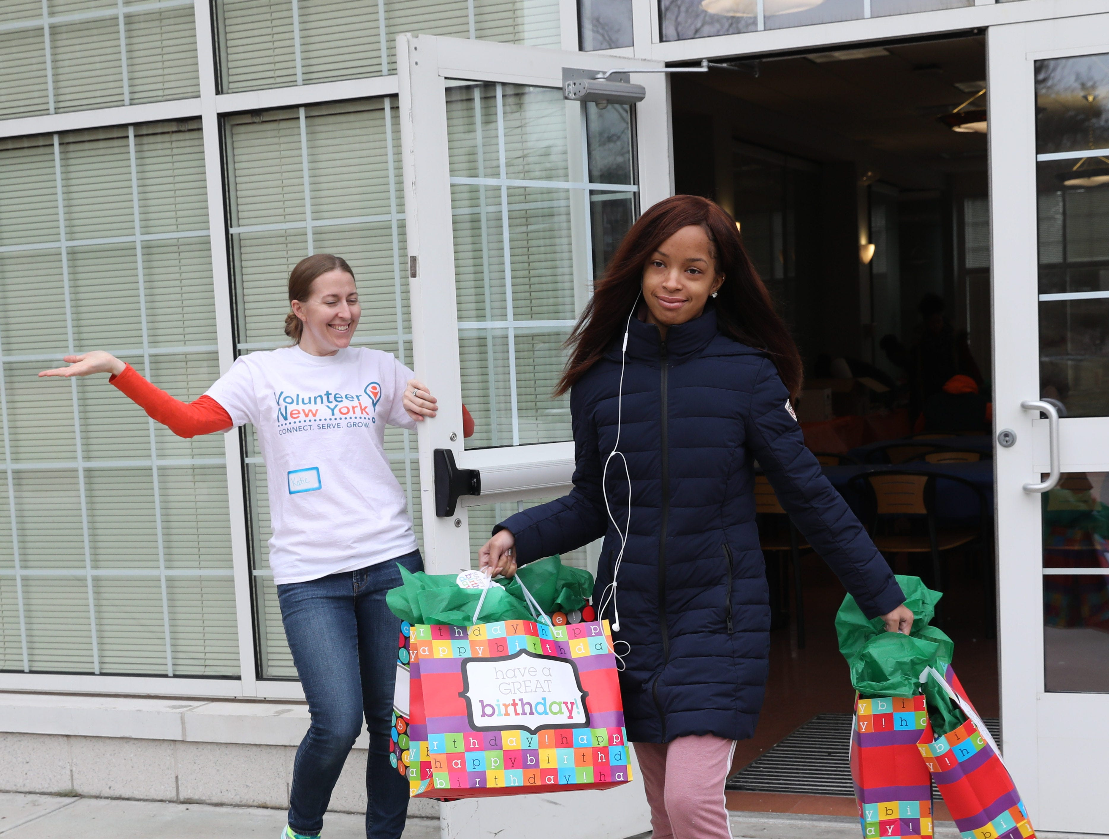 """Volunteer Brianna Ferrer carries out """"birthday bags"""" as Katie Pfeifer with Volunteer New York holds the door, during the Volunteer New York, Martin Luther King Jr. National Day of Service program at Dominican College in Orangeburg, Jan. 19, 2019. The birthday bags will be brought to the Nyack Center for distribution."""