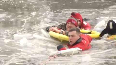 Rescuers crawl across 40 feet of ice to save man and dog from frozen pond