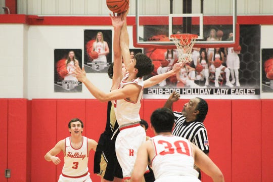 Holliday's Tucker Strealy and Henrietta's Riley Roye battle for the tip-off Friday. Strealy and the Eagles are leading the district.