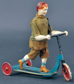The young red-headed boy on a scooter toy is made of metal, but he is dressed in a cloth suit. It was made by Victor Bonnet soon after World War I. Price, $1,560