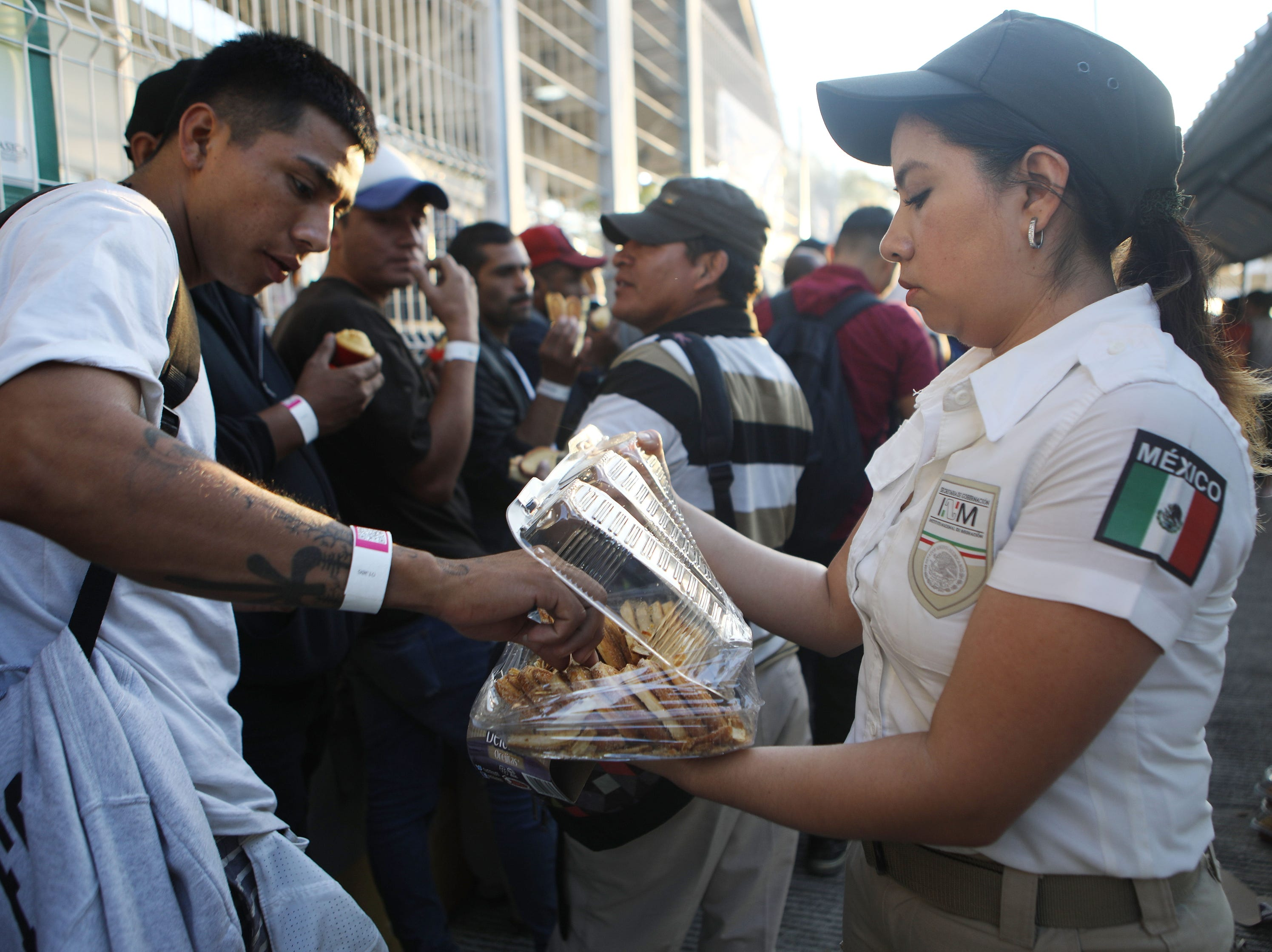 Central American migrants, part of a new 'migrant caravan', are given food by a Mexican immigration official after crossing a border bridge between Guatemala and Mexico to register at an immigration facility in Ciudad Hidalgo, Mexico.