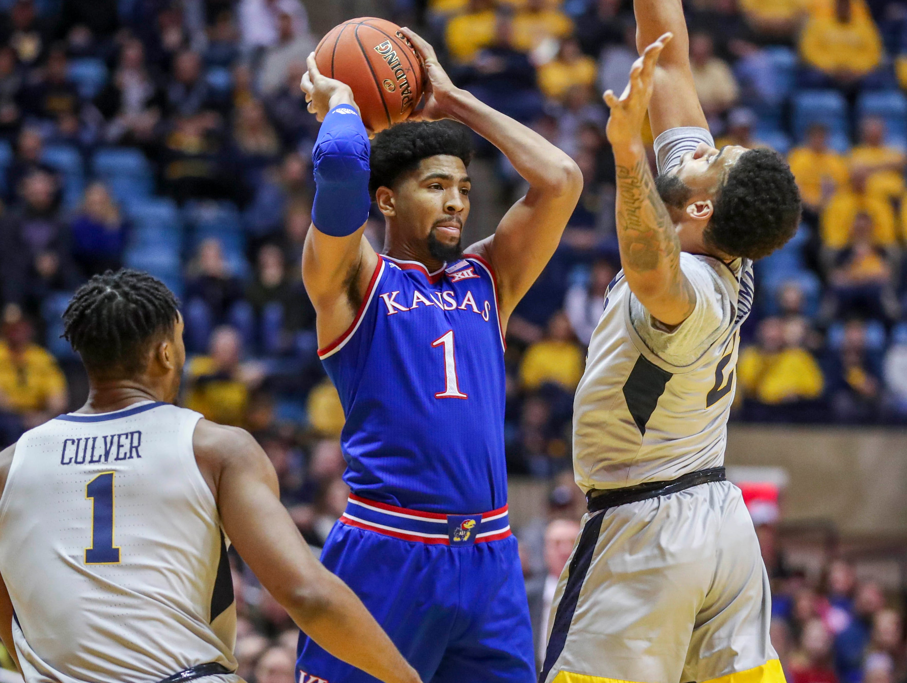 Jayhawks forward Dedric Lawson looked to pass while pressured by West Virginia's Esa Ahmad (23) on Saturday.
