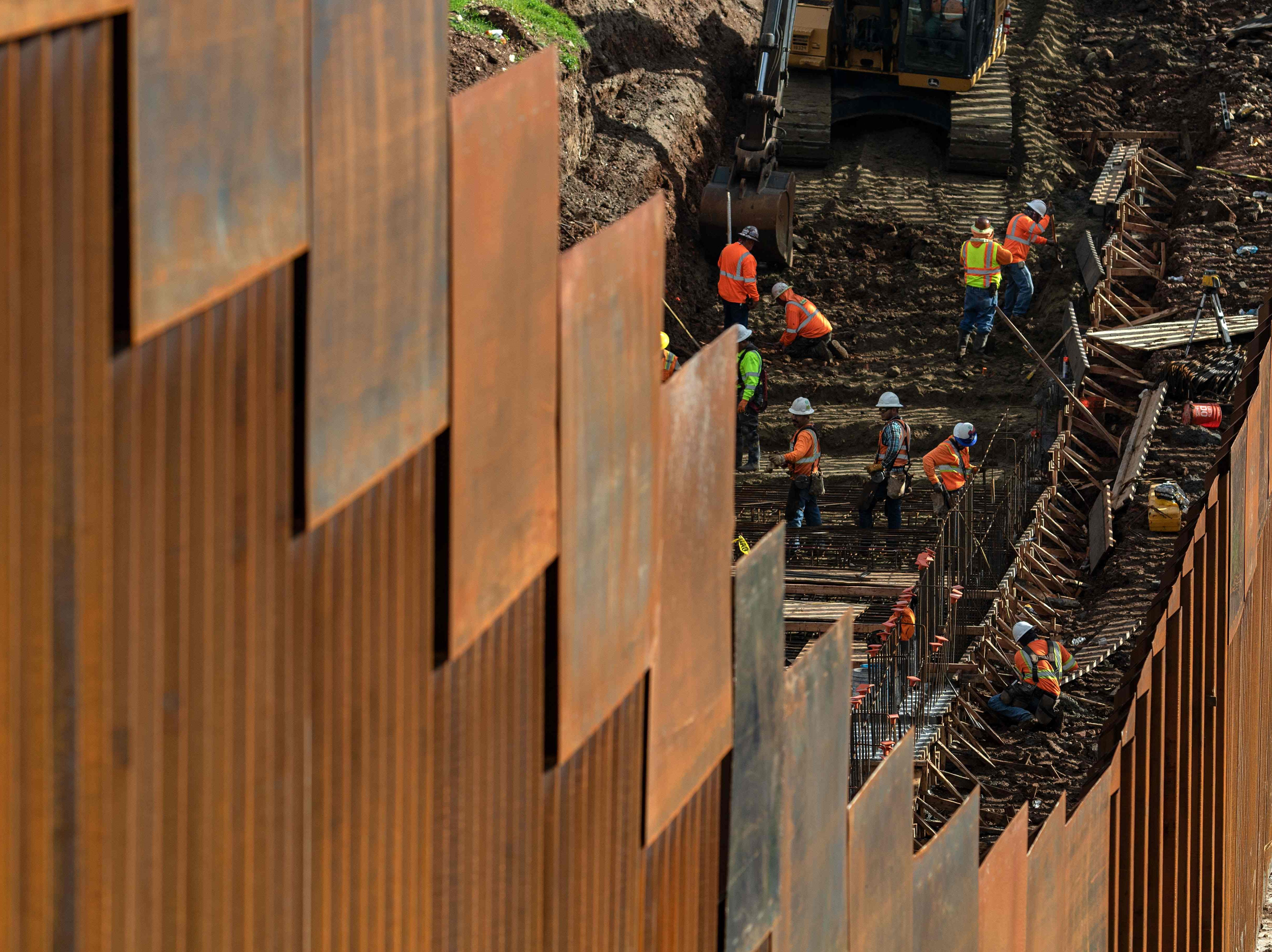 Workers reinforce a section of the US-Mexico border fence, as seen from eastern Tijuana, in Baja California state, Mexico, on Jan. 18, 2019.