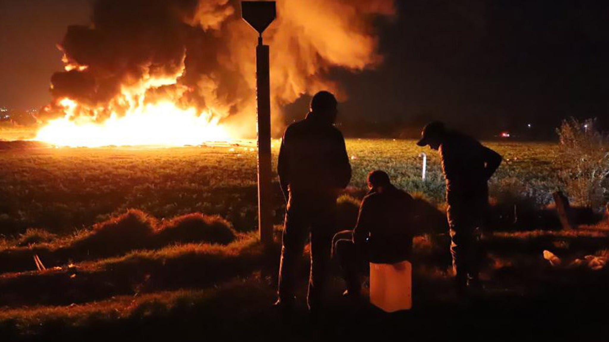 People wait in front of a wall of fire after an explosion of an illegal tap on Mexican oil company Pemex's pipeline in Tlahuilipan, state of Hidalgo, Mexico.
