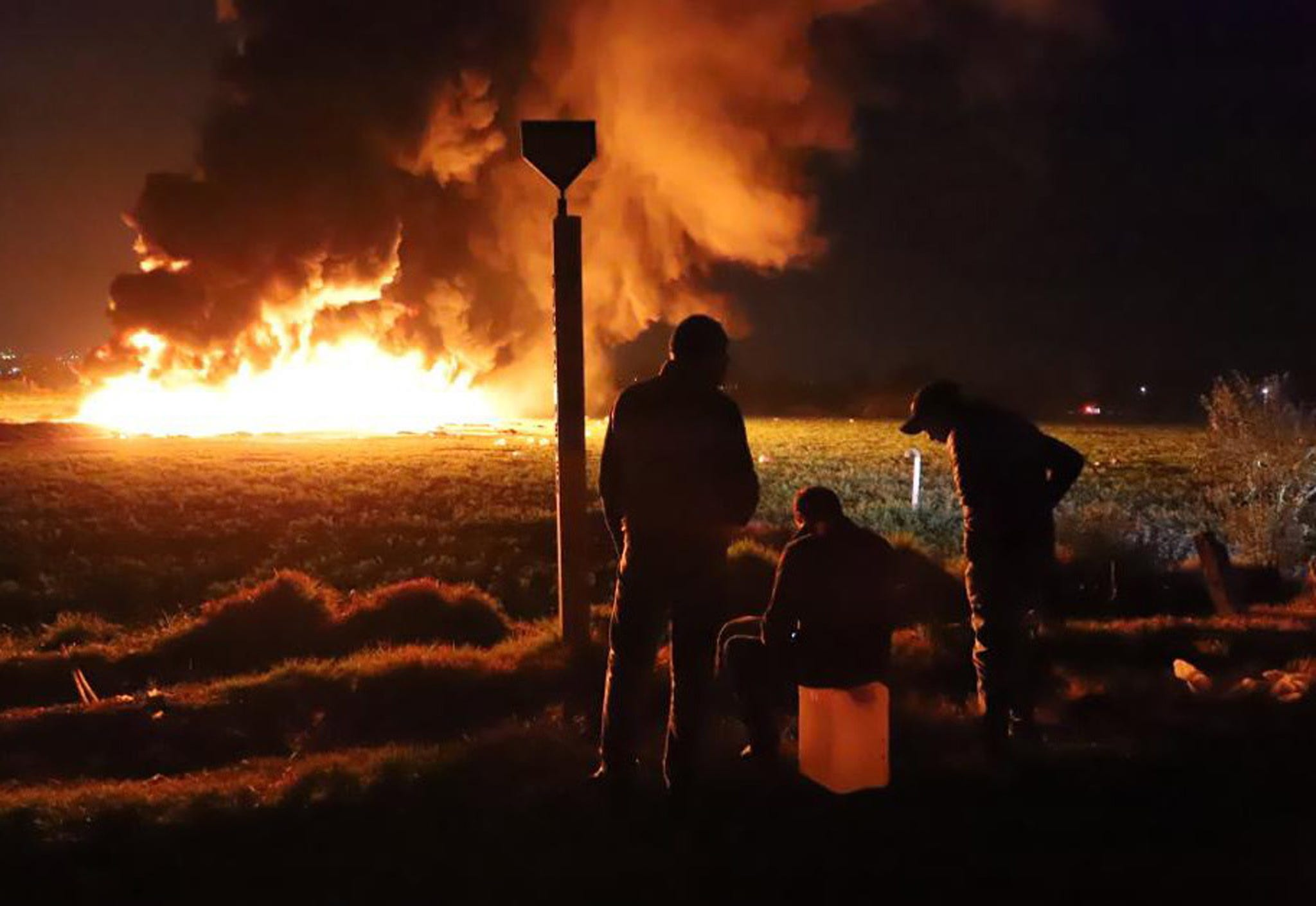 People are waiting in front of a wall of fire after an explosion of an ill equal loss on Mexican oil company Pemex pipeline in Tlahuilipan, state of Hidalgo, Mexico.
