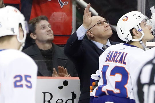 Former Washington Capitals' and current New York Islanders head coach Barry Trotz waves to the crowd from the bench during a video tribute in the first period at Capital One Arena.