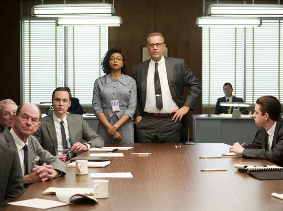 """Taraji P. Henson (standing left) and Kevin Costner (standing right) appear in the 2016 film """"Hidden Figures."""""""