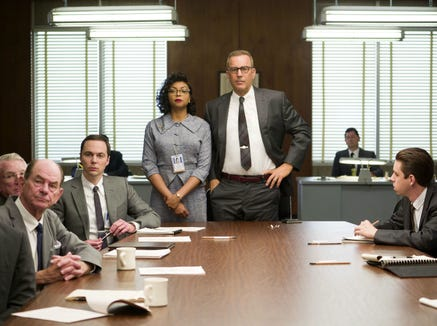 "Taraji P. Henson (standing left) and Kevin Costner (standing right) appear in the 2016 film ""Hidden Figures."""