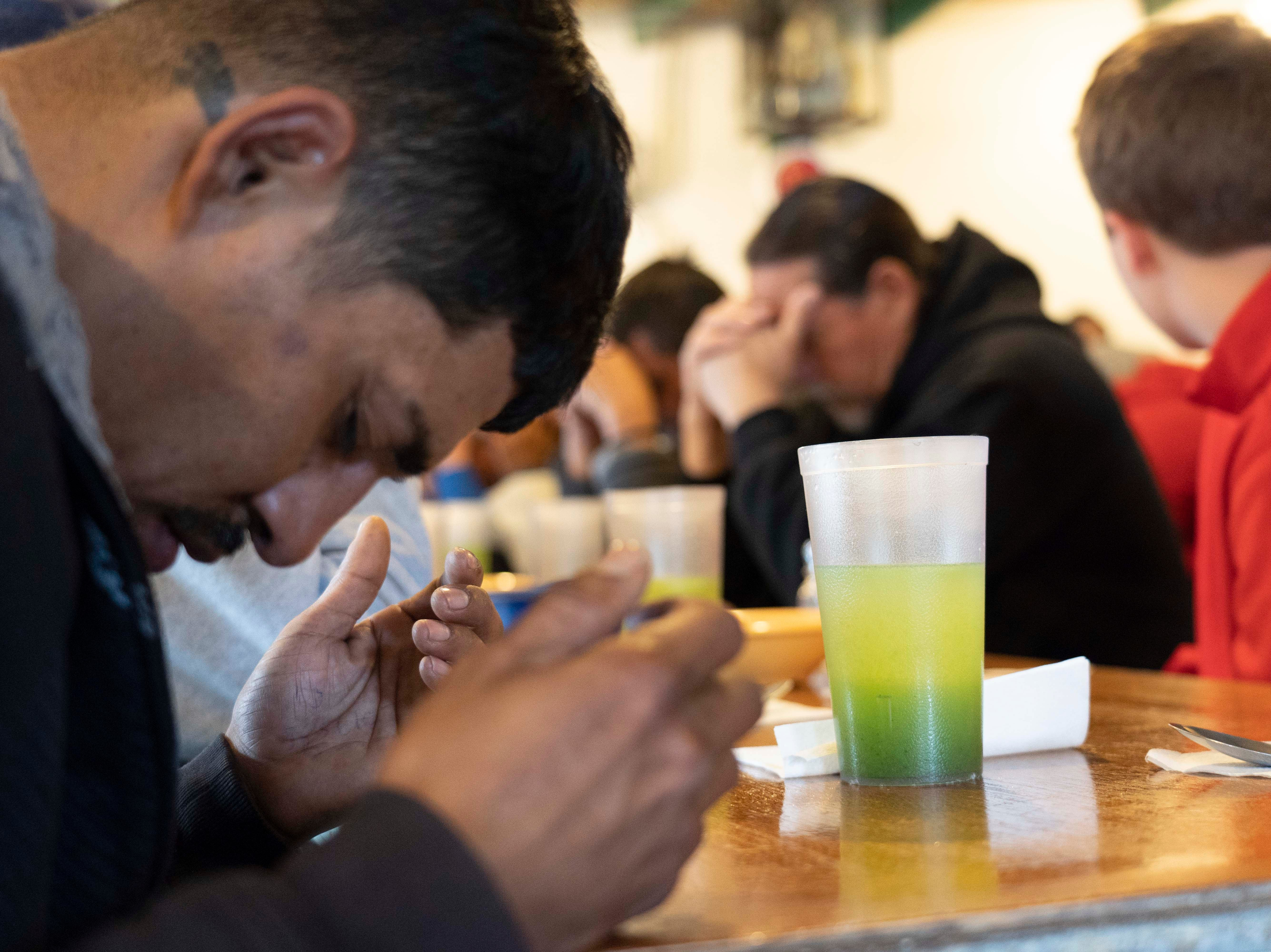 Migrants pray at Kino Border Initiative shelter in Sonora, Mexico after being deported from the United States on Jan. 18, 2019.