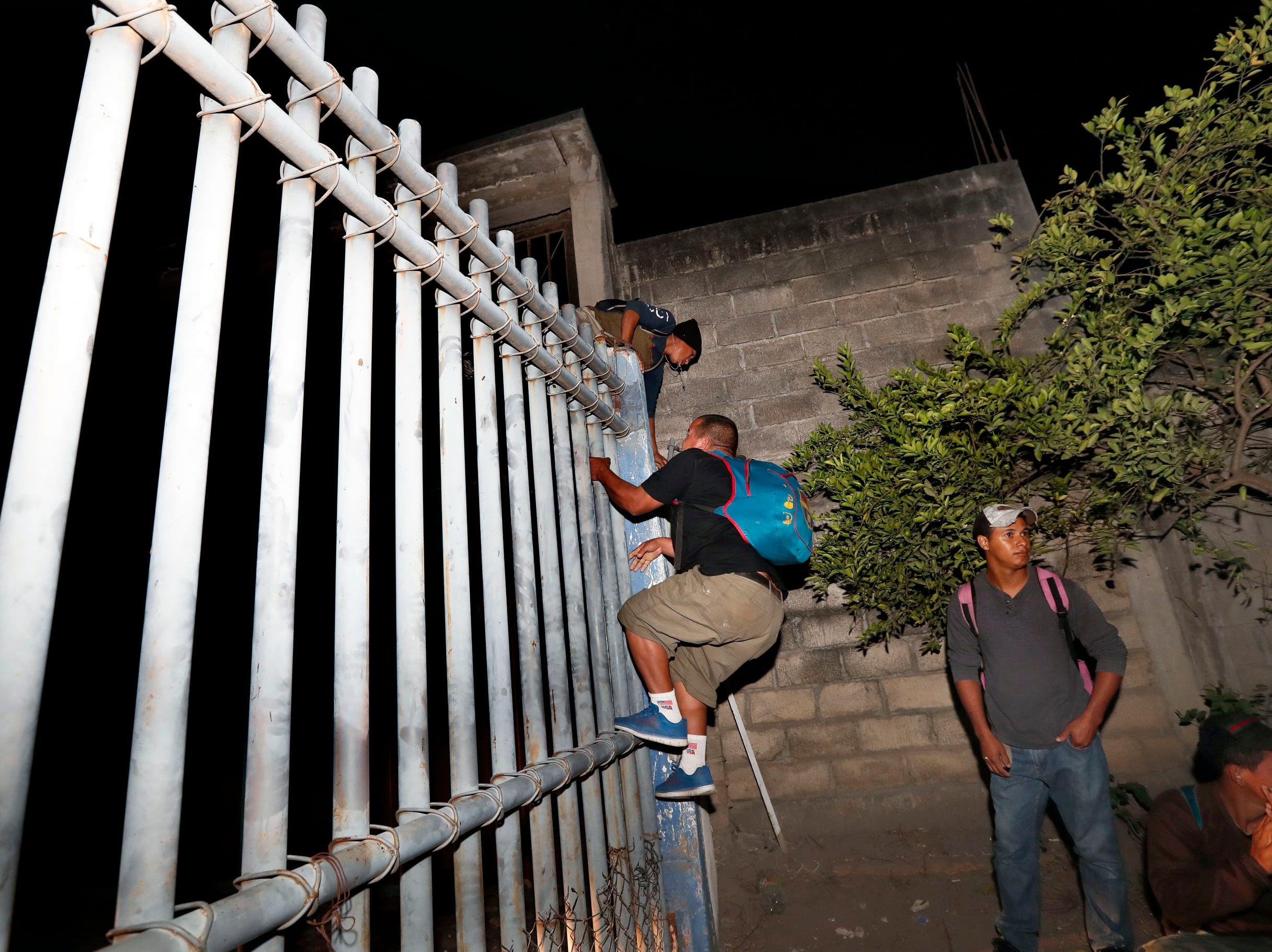 Honduras migrants climb over the fence into Mexico, at the border between Mexico and Guatemala near Ciudad Hidalgo, Chiapas State, Mexico, on Jan. 18,2019. Hundreds of Central American migrants are walking and hitchhiking through the region as part of a new caravan of migrants hoping to reach the United States.